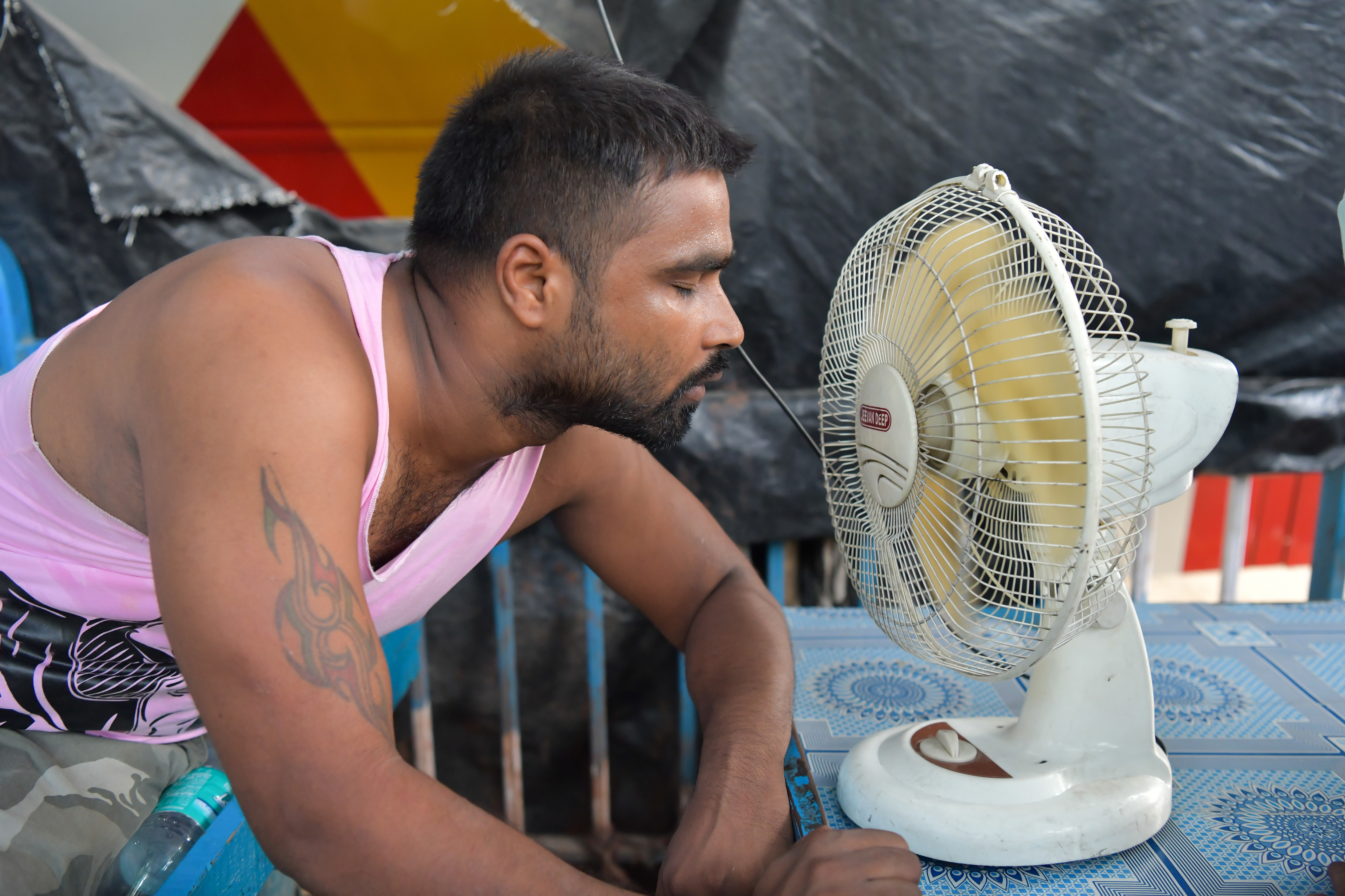 A man is seen taking a break from work cooling himself down...