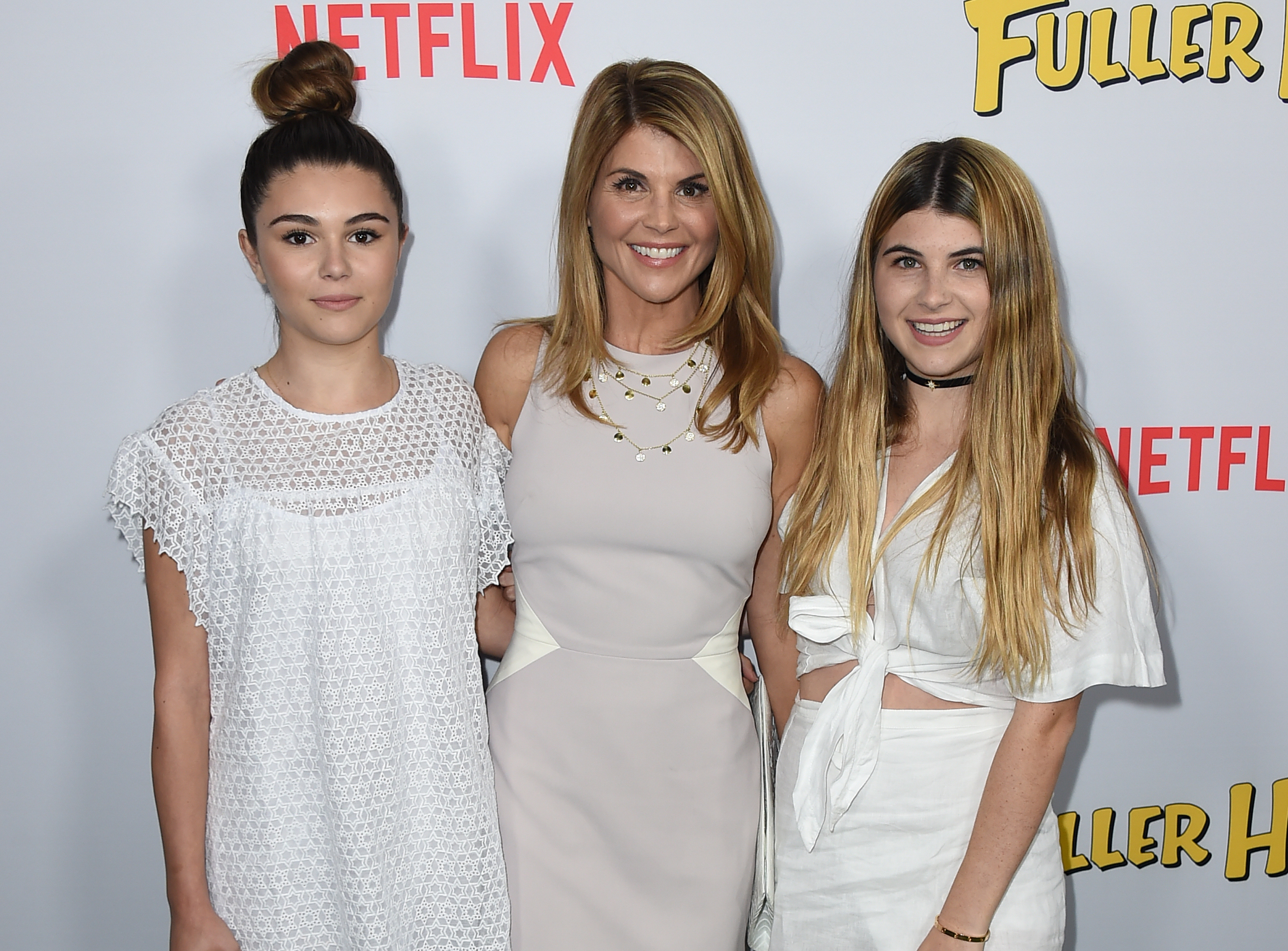 """Lori Loughlin, center, and her daughters Isabella Rose Giannulli and Olivia Jade Giannulli attend the premiere of """"Fuller House"""" on Feb. 16, 2016, in Los Angeles."""