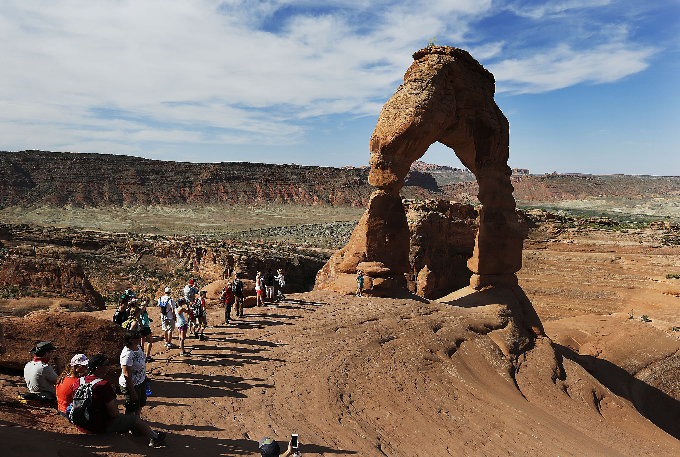 Tourists line up for photos at Delicate Arch in Arches National Park near Moab on Friday, June 3, 2016.