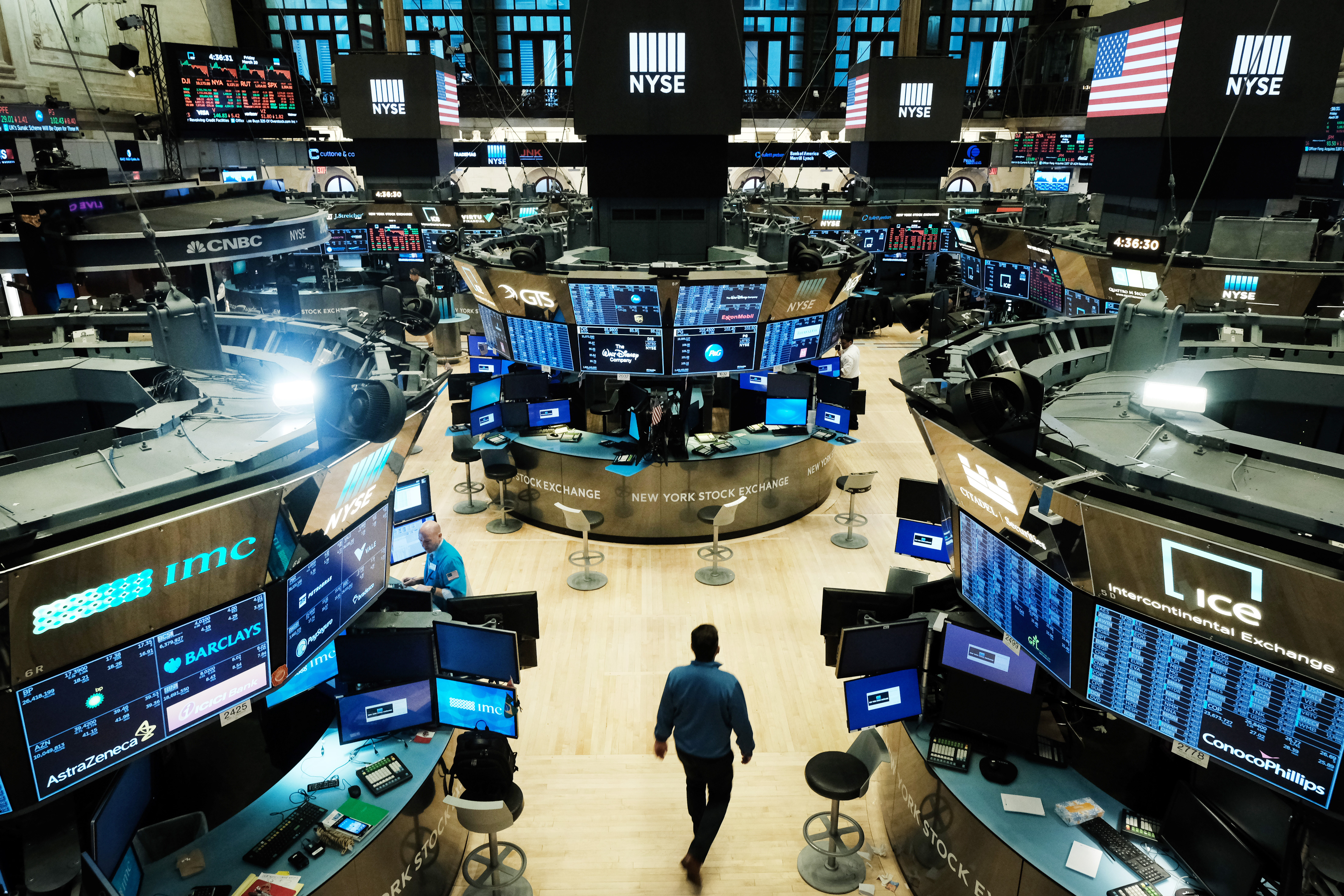 A man walks through an empty trading floor at the New York Stock Exchange.