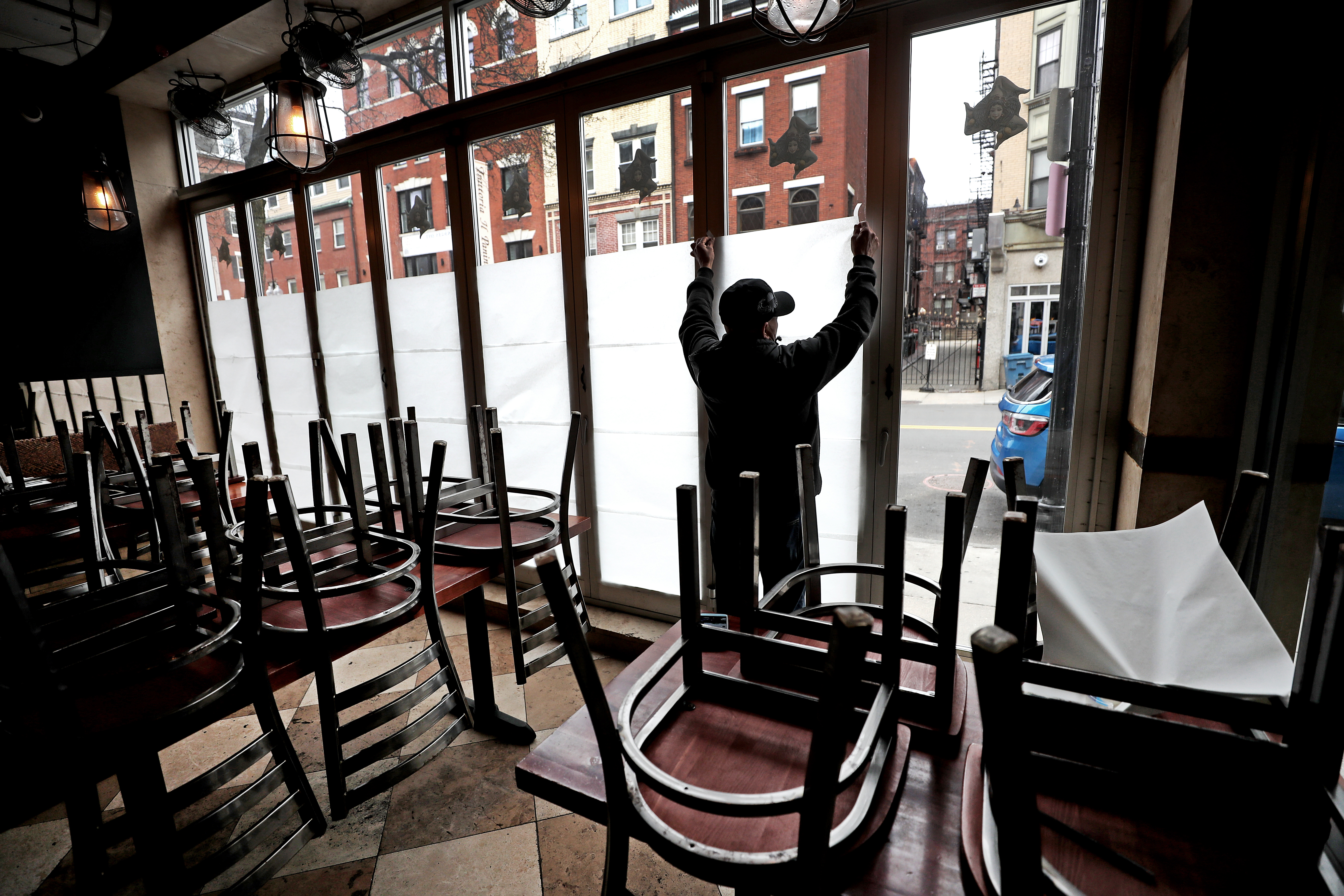 Man putting up paper over restaurant windows amid chairs stacked on top of tables.