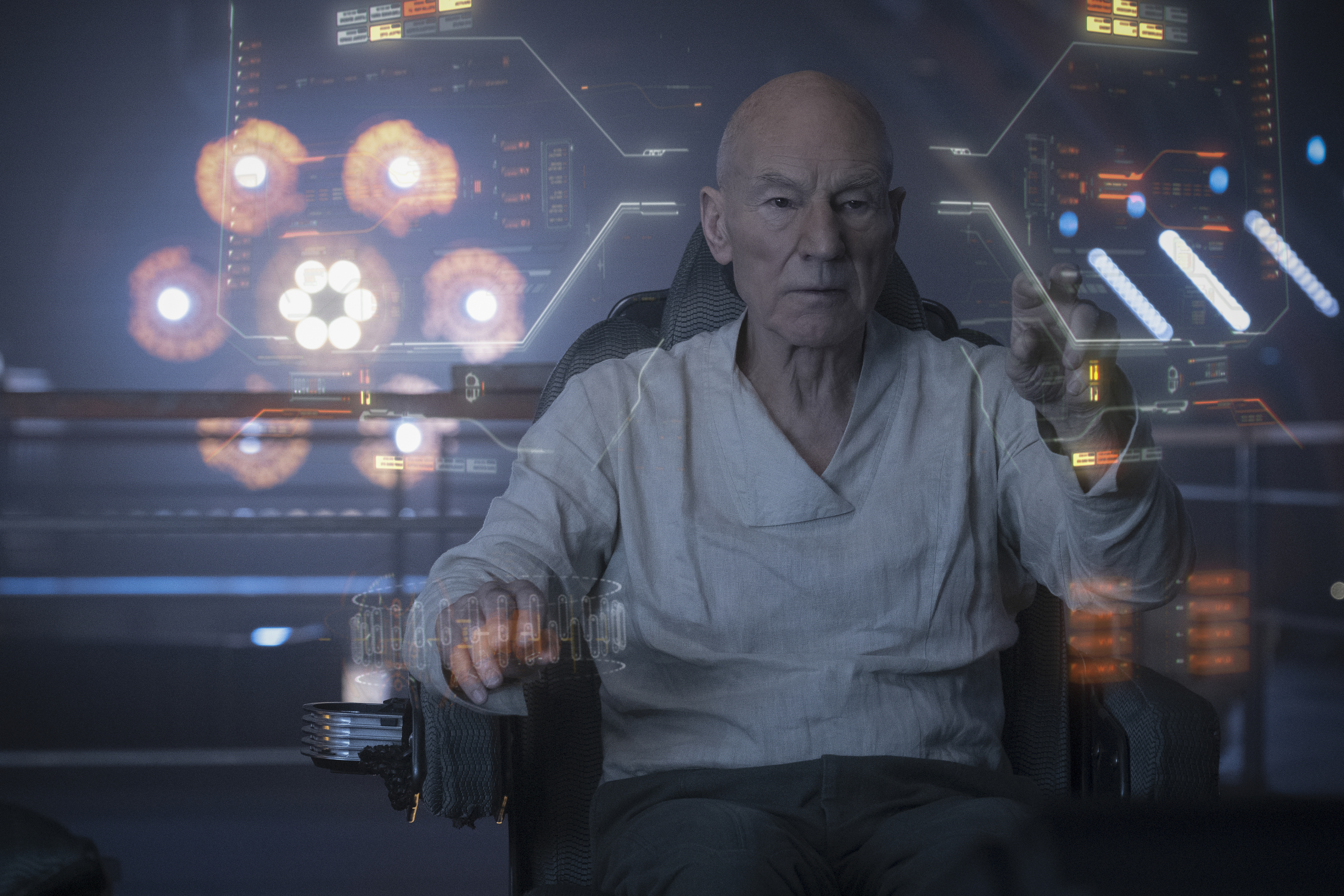 Patrick Stewart as Jean-Luc Picard pilots a ship, surrounded by virtual heads-up displays