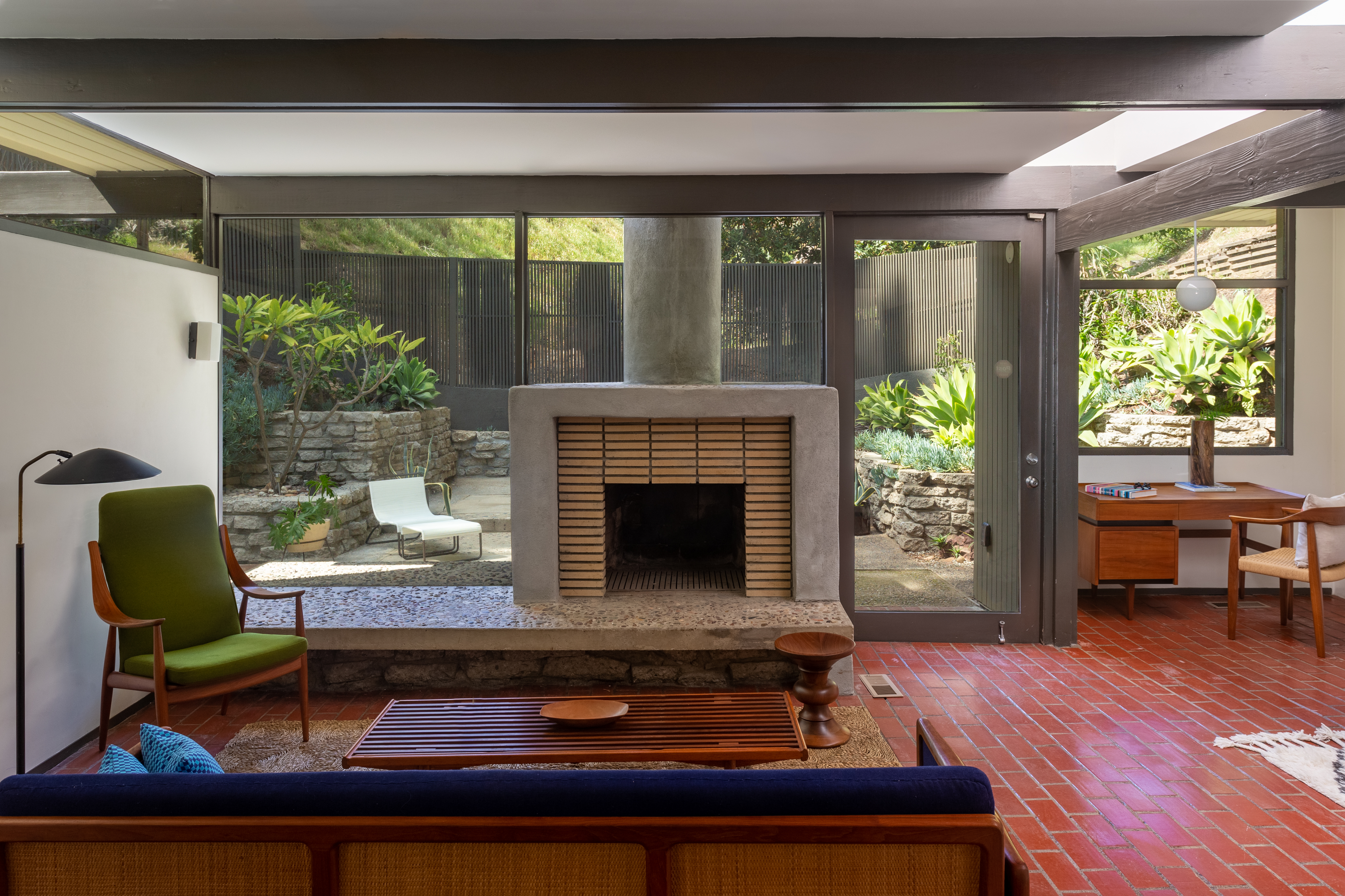 A room with brick floors, glass walls, and a fireplace