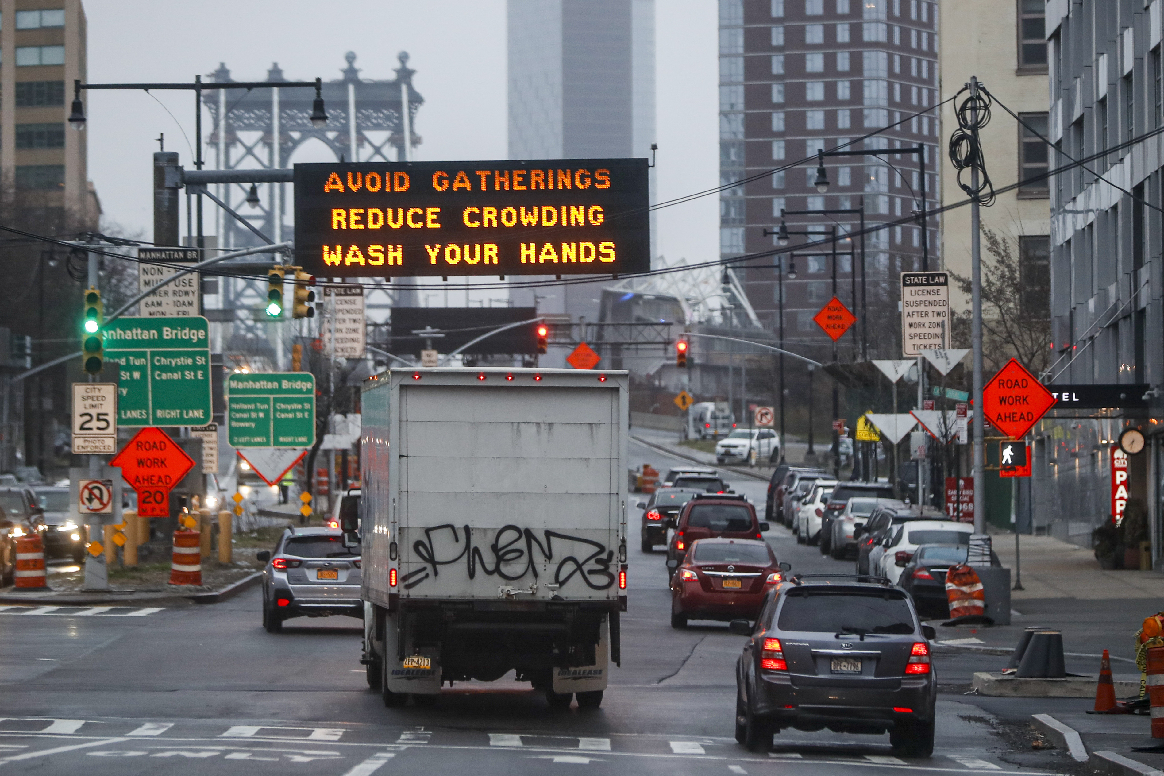 A sign displaying messages on how to reduce the spread of COVID-19, the disease caused by the new coronavirus, is displayed at the mouth of the Manhattan Bridge, Monday, March 23, 2020, in the Brooklyn borough of New York. (AP Photo/John Minchillo)