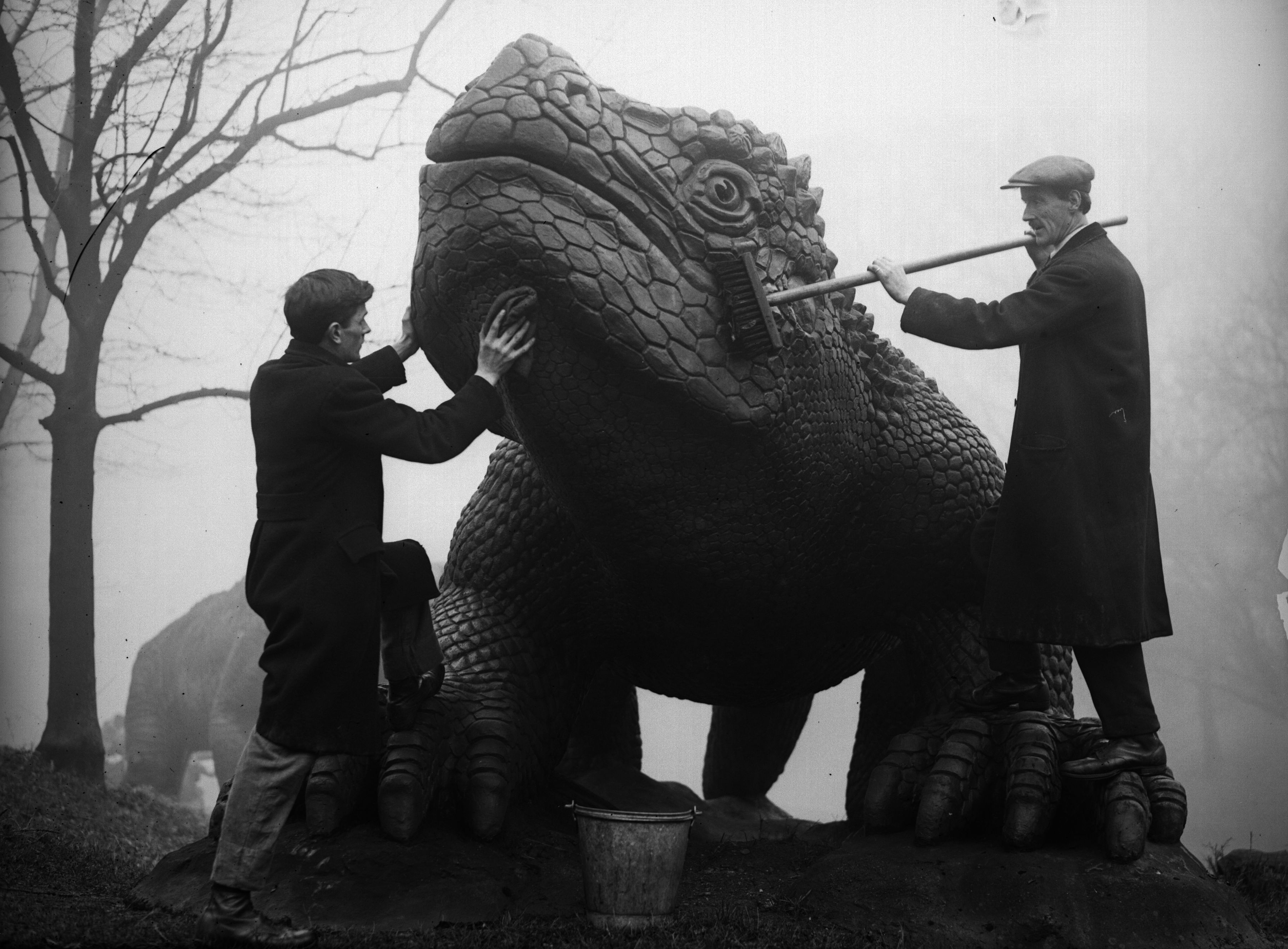 Cleaning a dinosaur statue at Crystal Palace