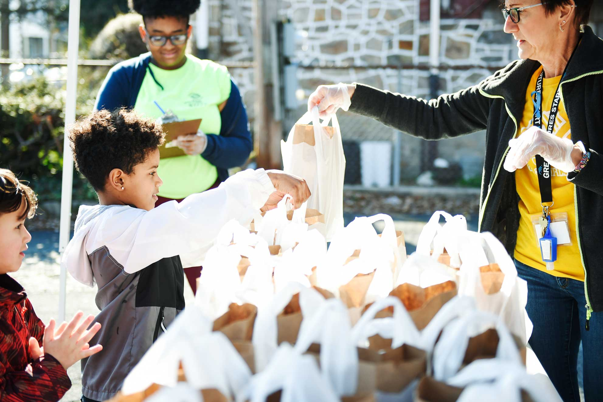 Two boys handles plastic bags of food from a woman at a table filled with bagged lunches.