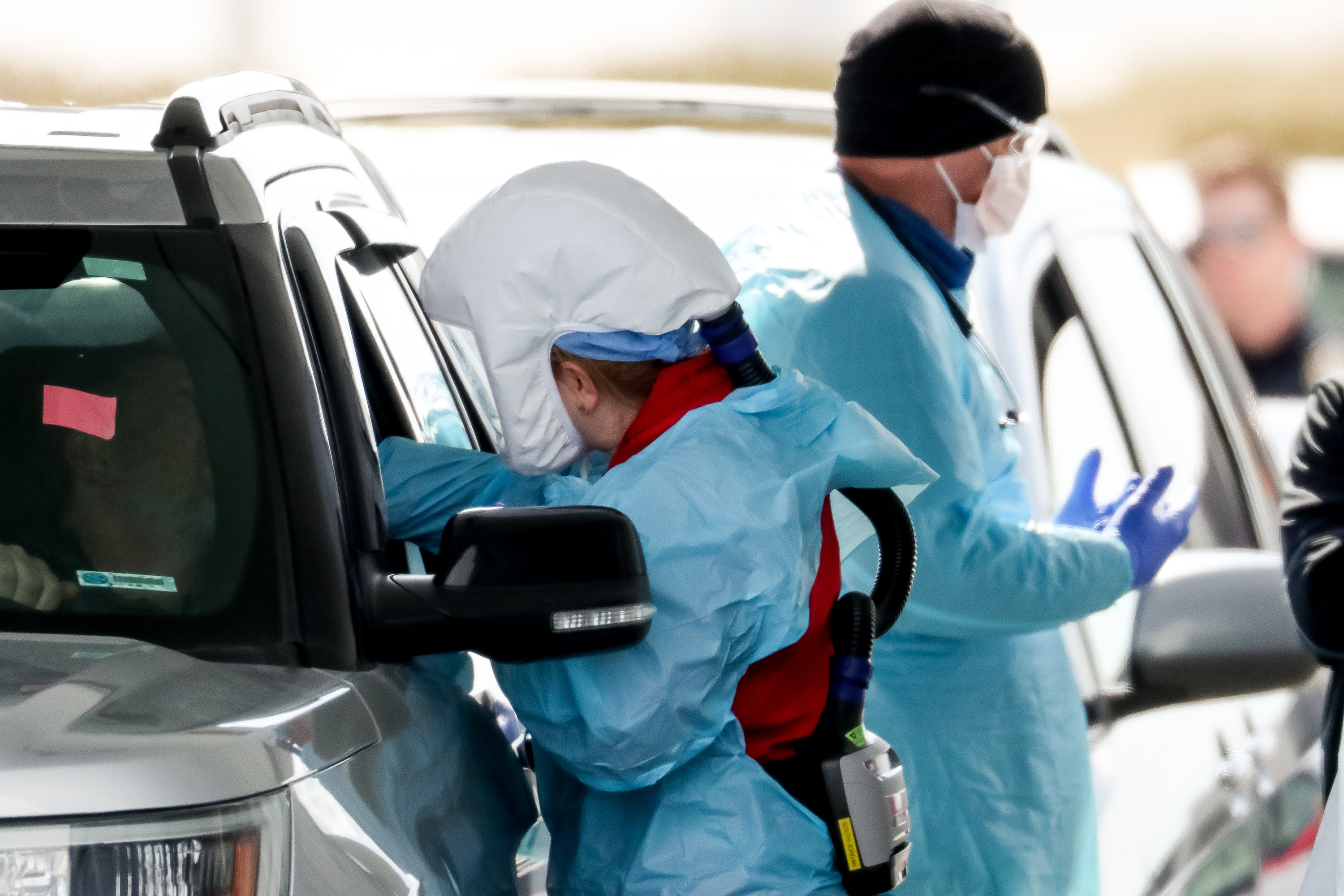 Medical workers provide drive-thru COVID-19 testing at University of Utah Health's South Jordan Health Center in South Jordan on Friday, March 27, 2020.