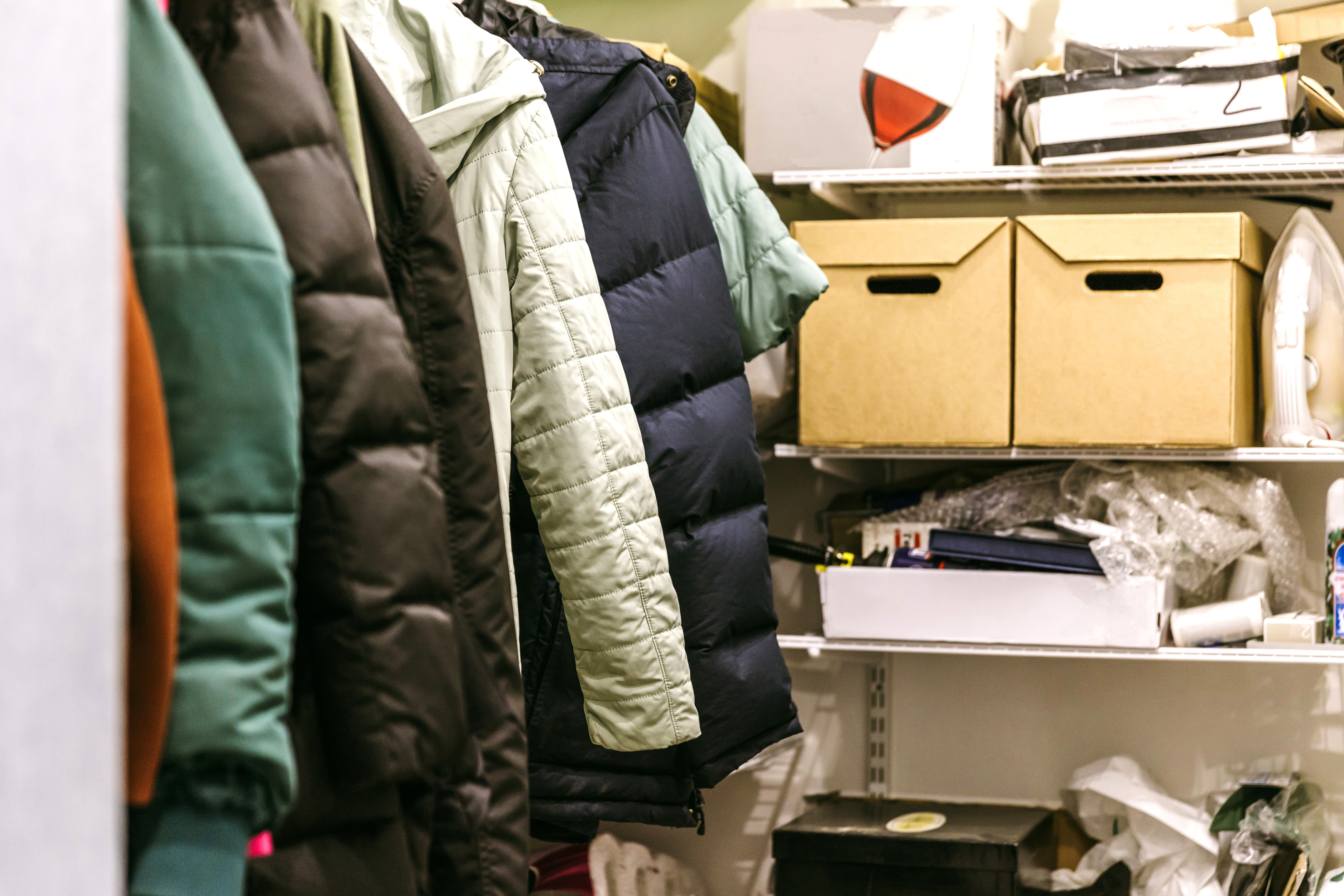 A somewhat cluttered closet with winter coats hanging up and boxes and other things crammed onto shelves at the end.