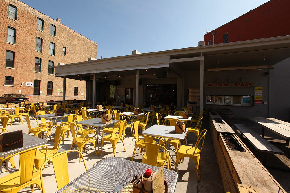 A bar's patio filed with yellow metal chairs.