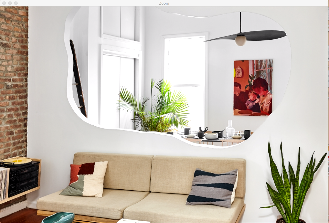 A tan couch is in the foreground with a plant next to it. Behind it, through a wall cutout, you can see a dining room table.