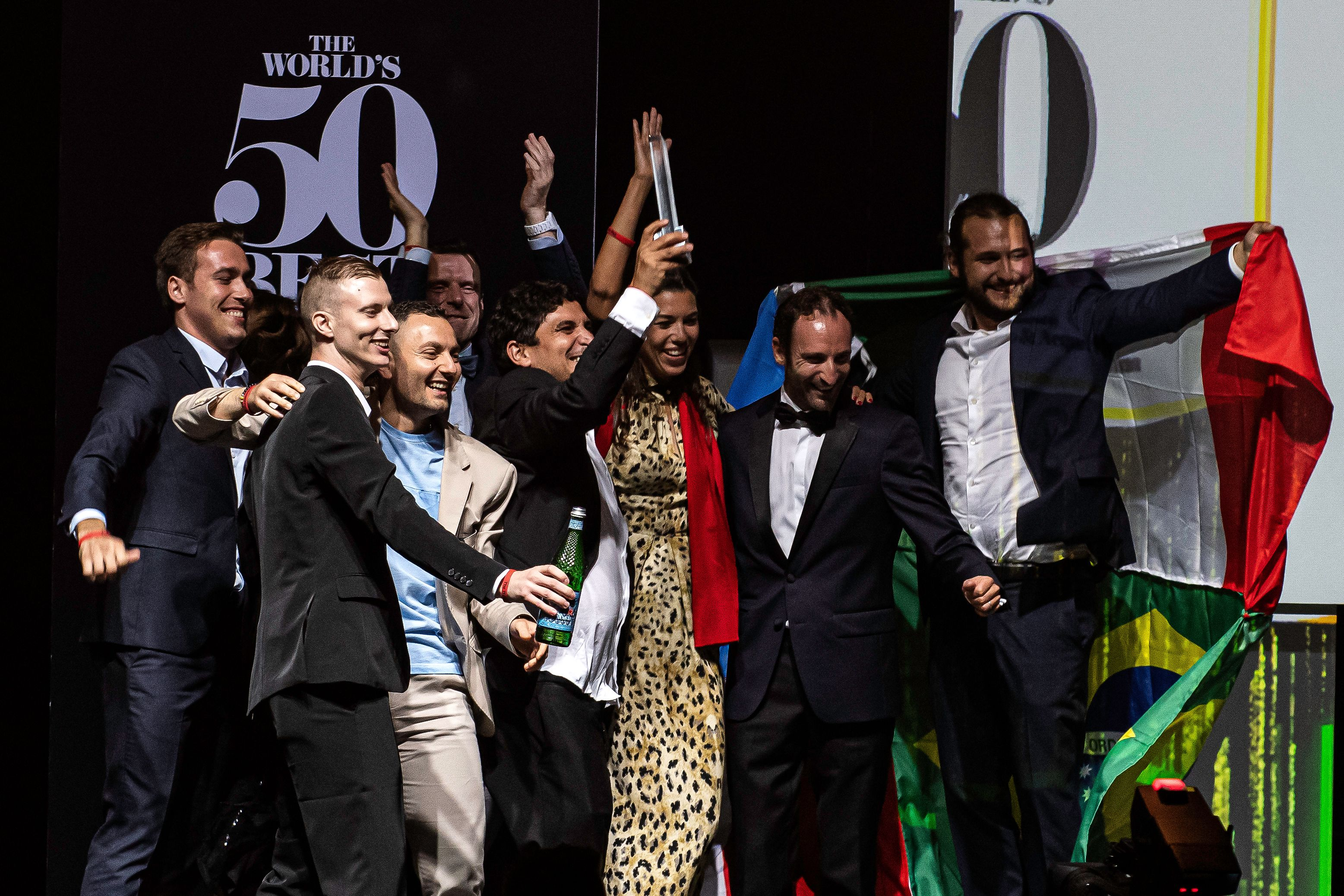 A group of people celebrate on stage after winning an award