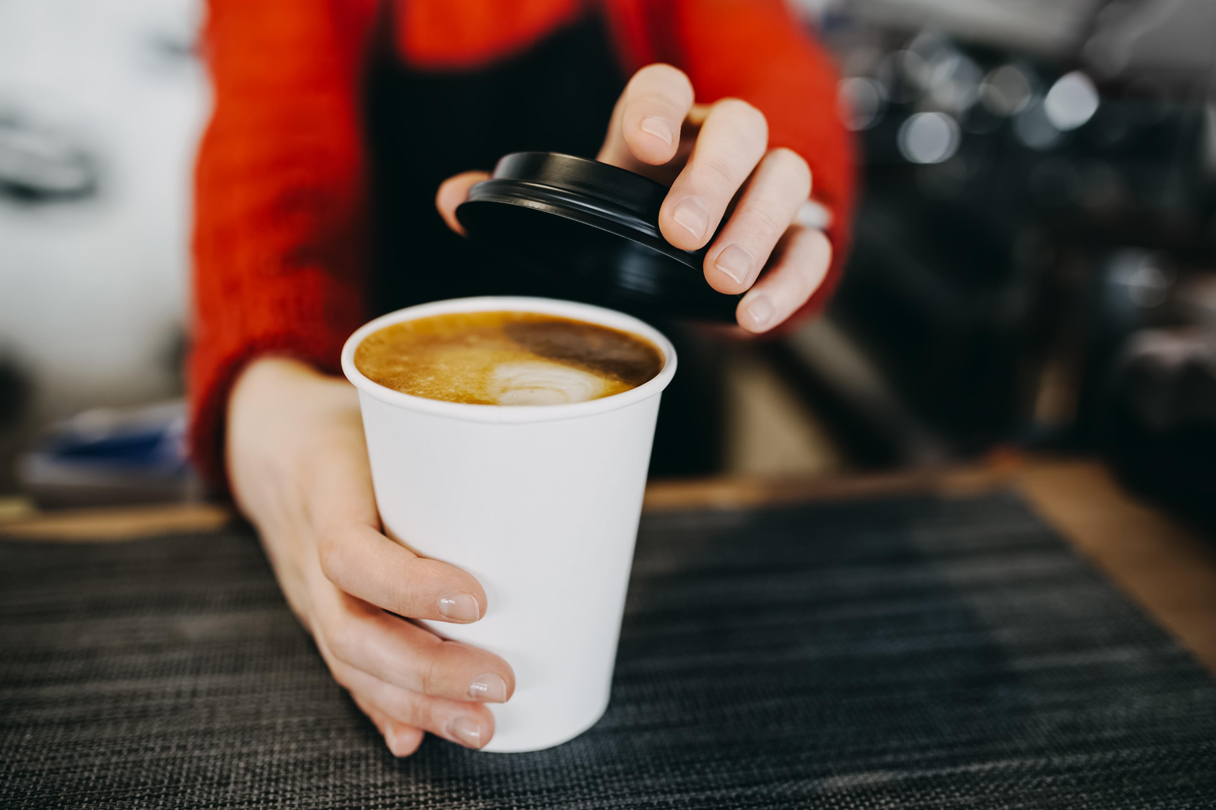 A barista handing over a white cup of coffee.