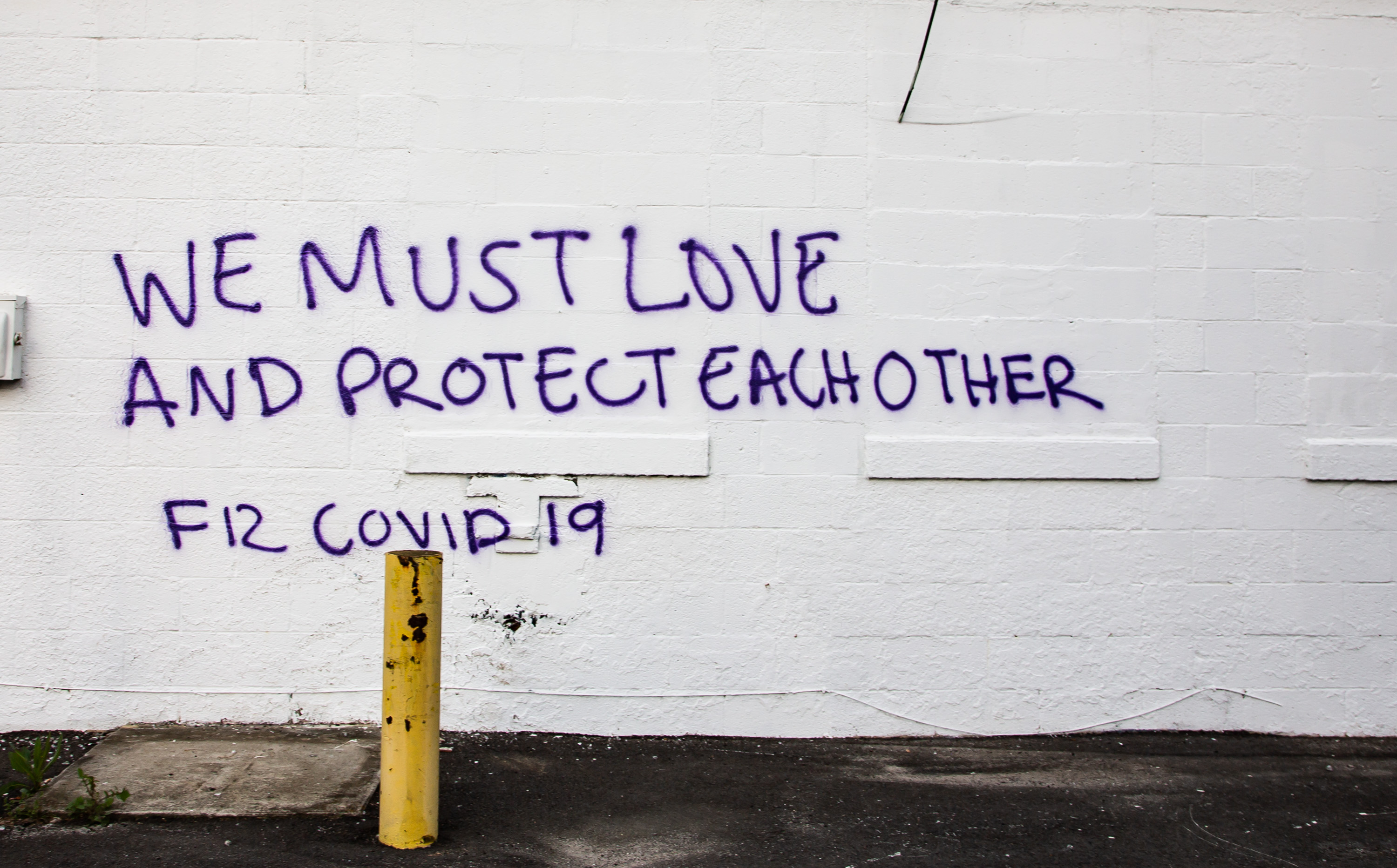 Spray painted We Must Love and Protect Each Other From COVID-19 on the side of a building for lease at the corner of Boulevard and Memorial Drive in Cabbagetown