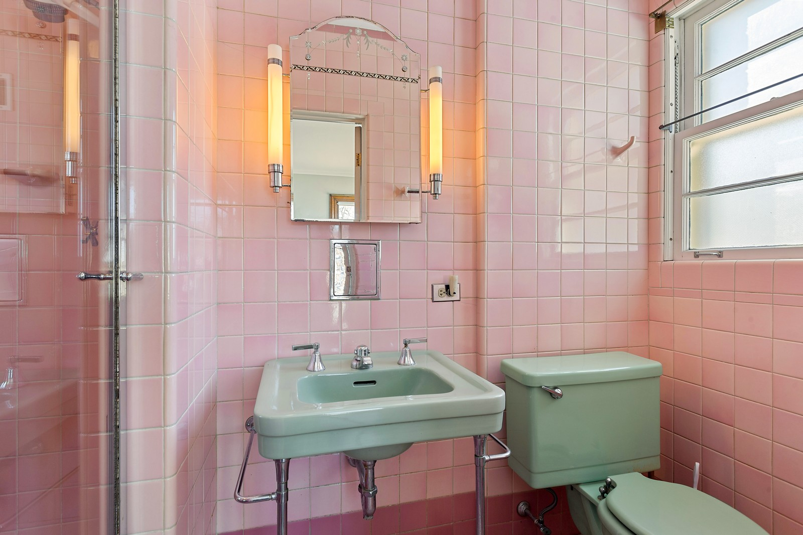 The bathroom with pink tiling and a seafoam green toilet and sink.
