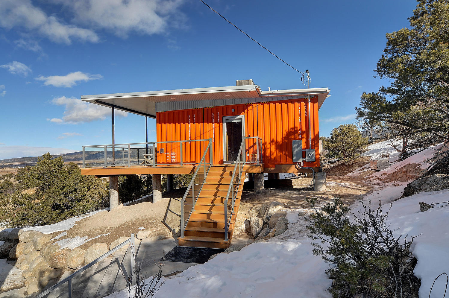 Stairs lead up to a bright orange shipping container house.