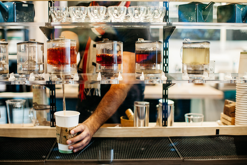 Red tea brews in siphons and pours into a white to-go cup at Eli Tea.