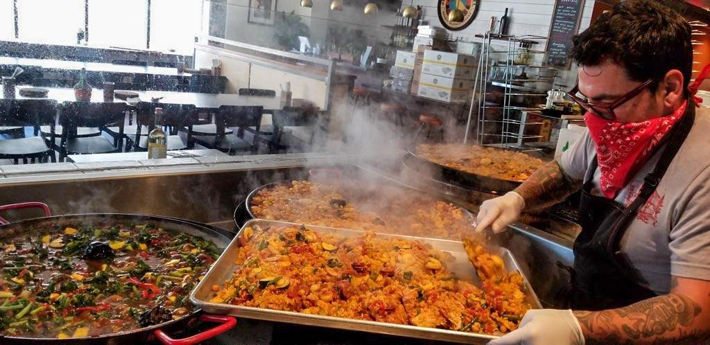 A cook prepares a pan of paella at Gerard's Paella