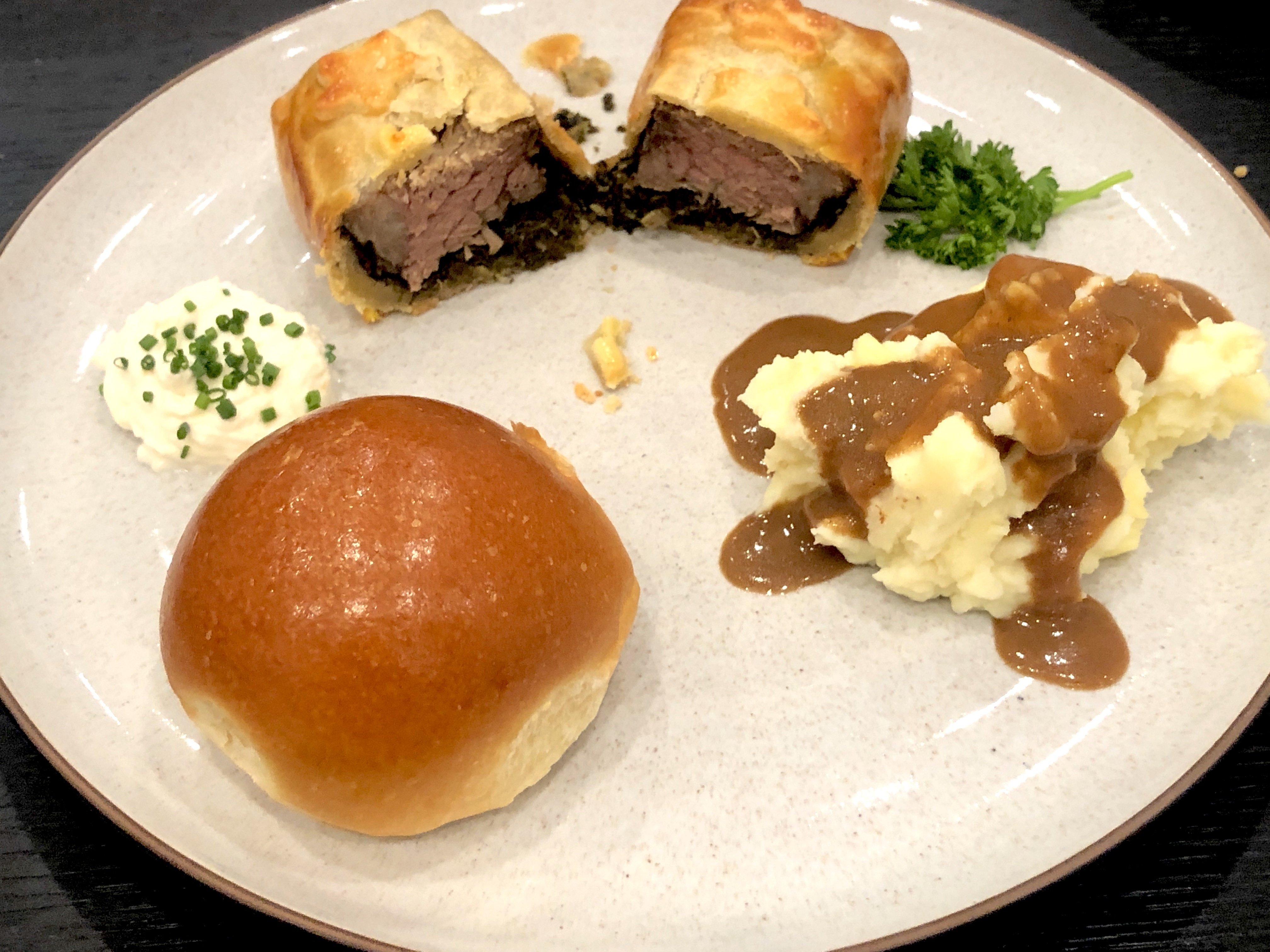 A plate with a dinner roll, beef Wellington, mashed potatoes, and creme fraiche.