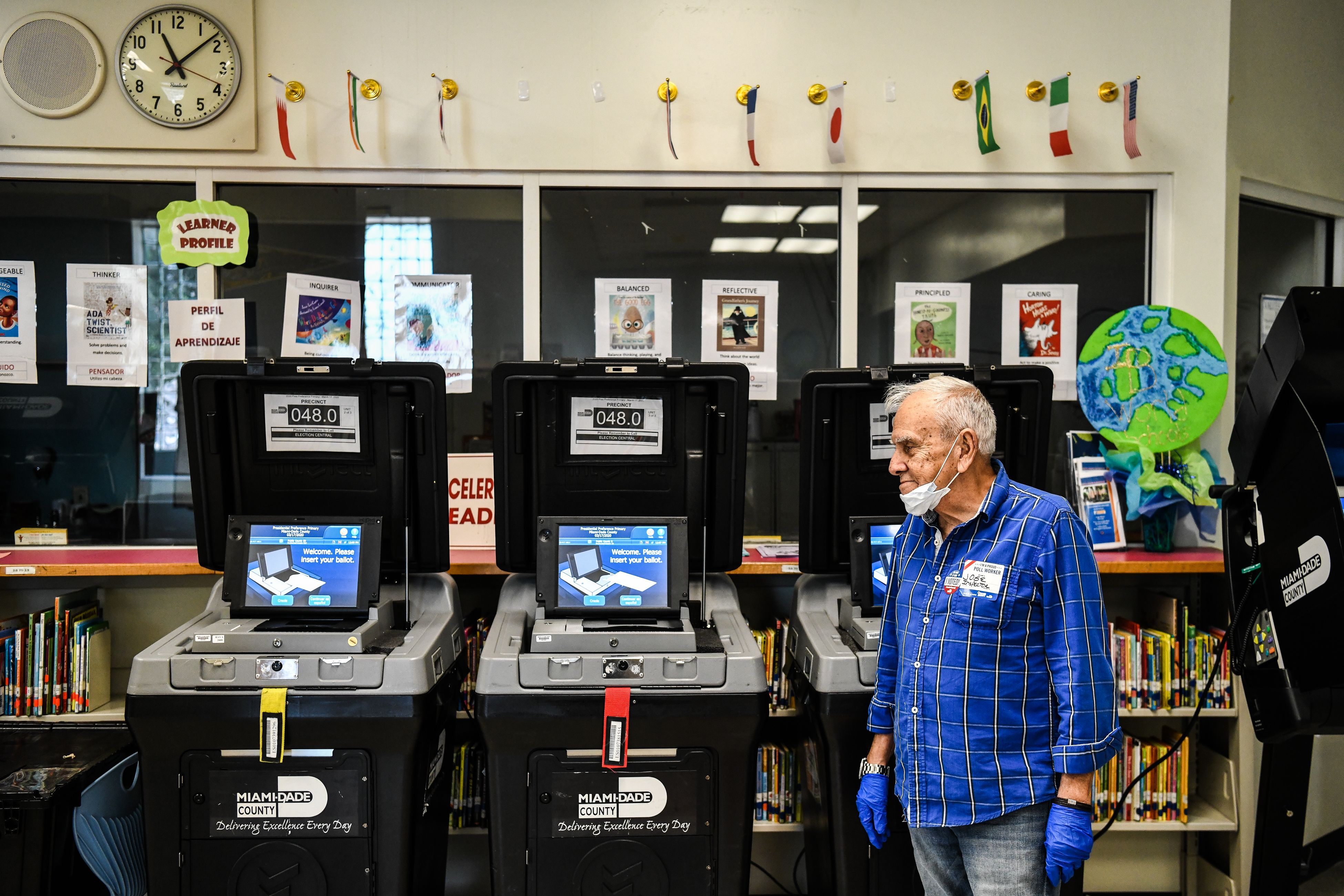 In a classroom full of books, three polling stations sit empty. A man in a blue shirt, with blue nitrile gloves and a face mask on his chin, stands next to them.