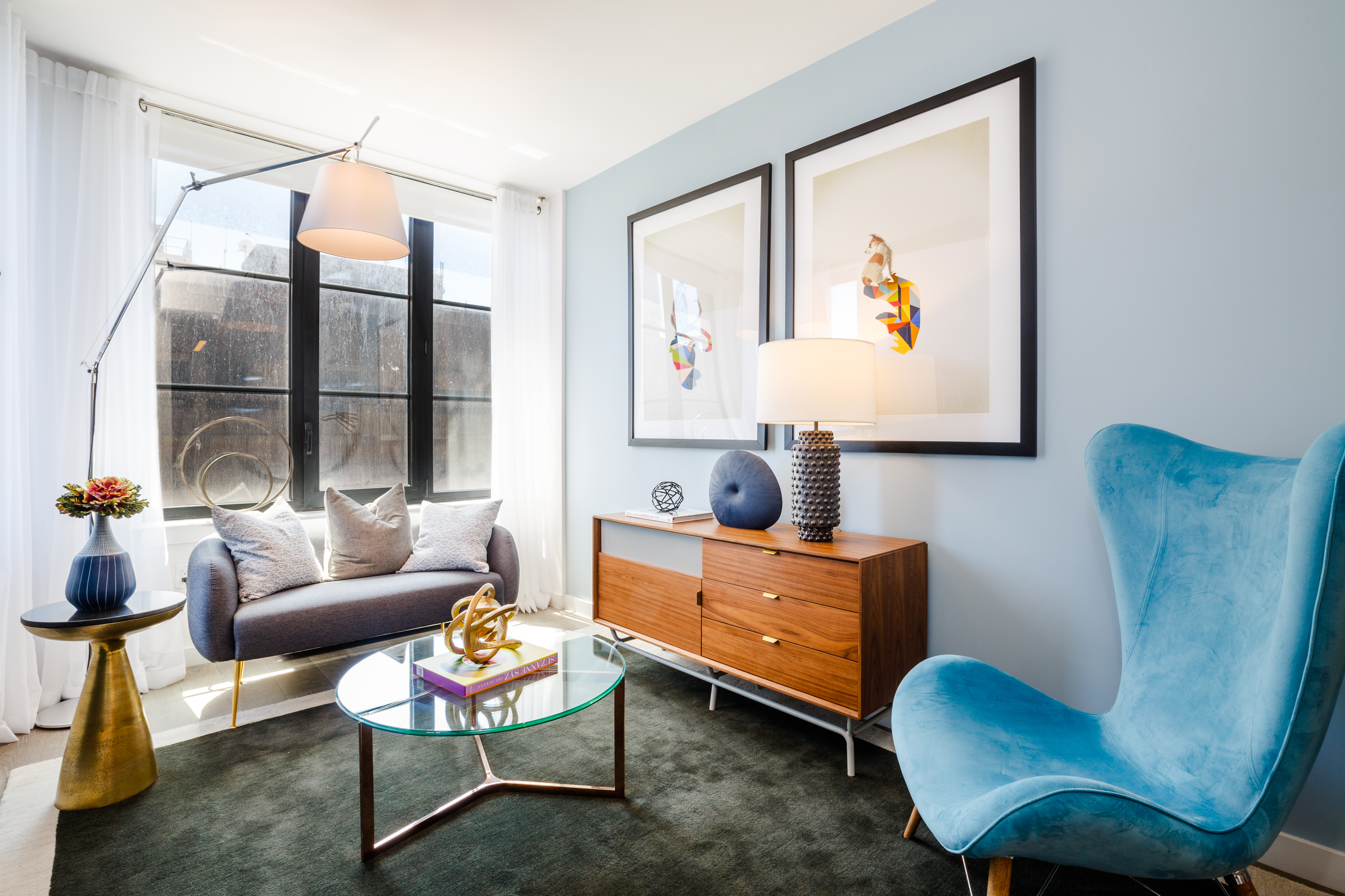 A living area with light blue walls, a large window, a standing lamp, a glass coffee table, and a blue chair.