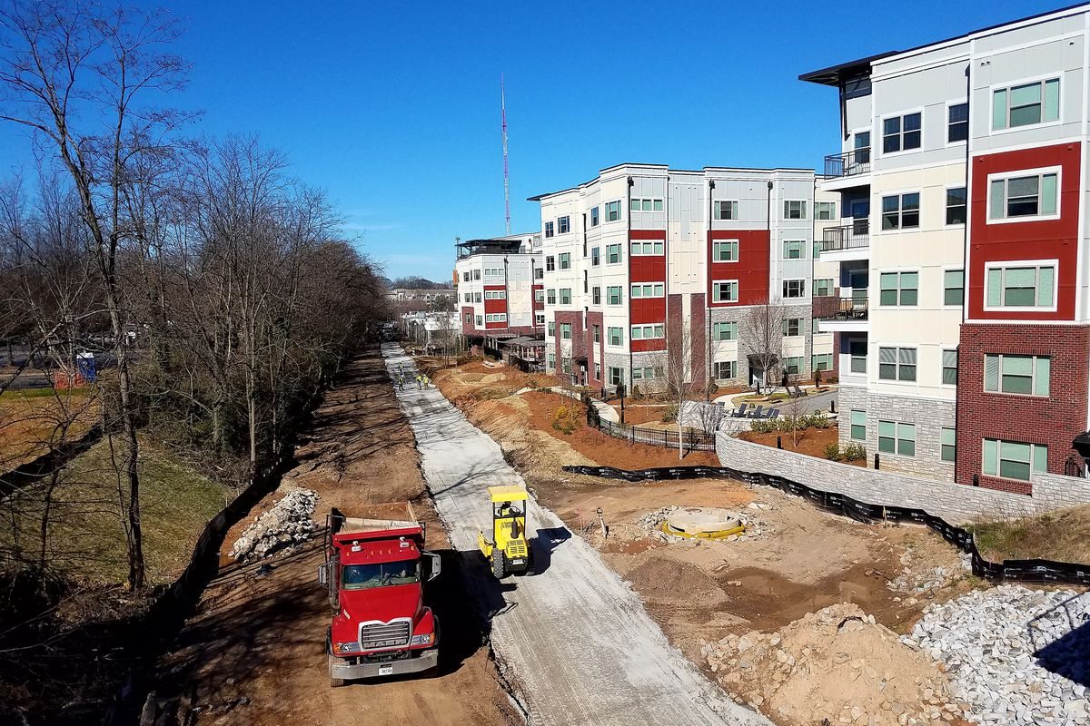 A trail being constructed next to two buildings in a city setting.