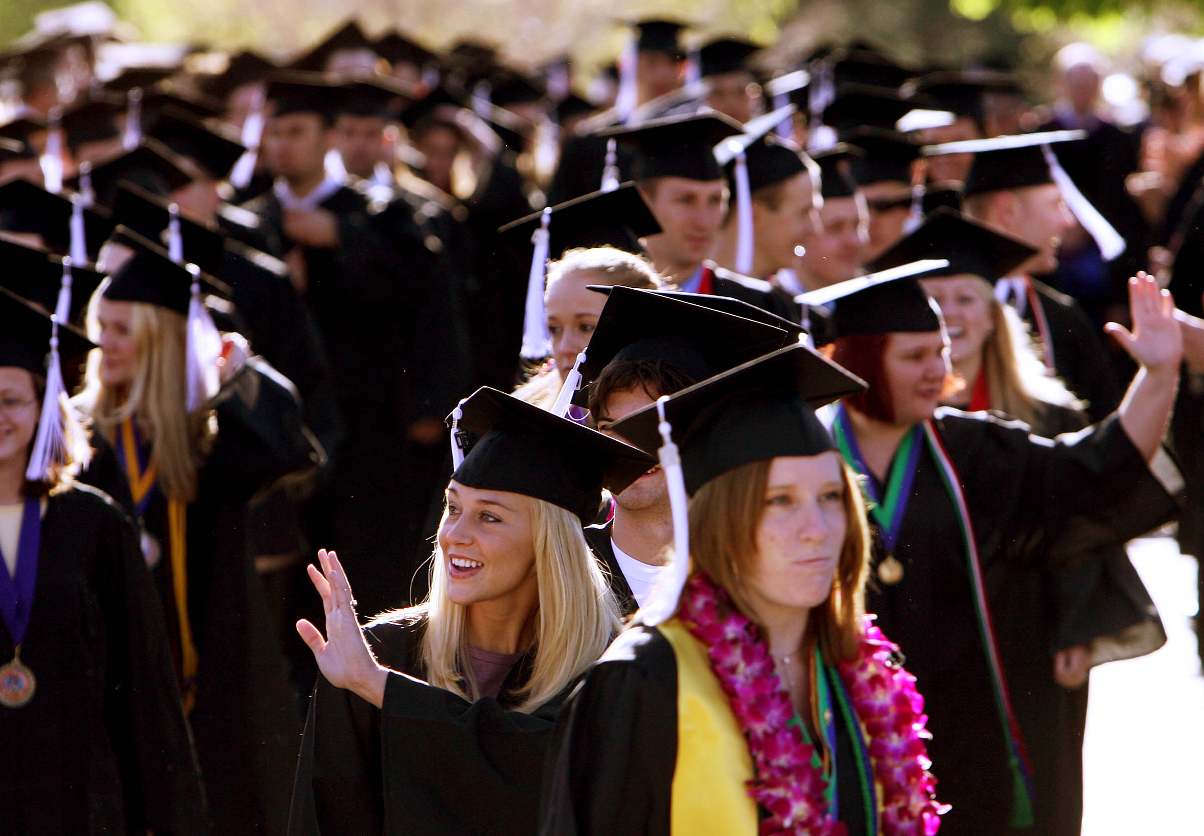Graduates wave and look for family and friends as they take part in the procession at the beginning of Southern Utah University Commencement in Cedar City, Utah, May 6, 2006. photo by Ravell Call, Deseret Morning News.