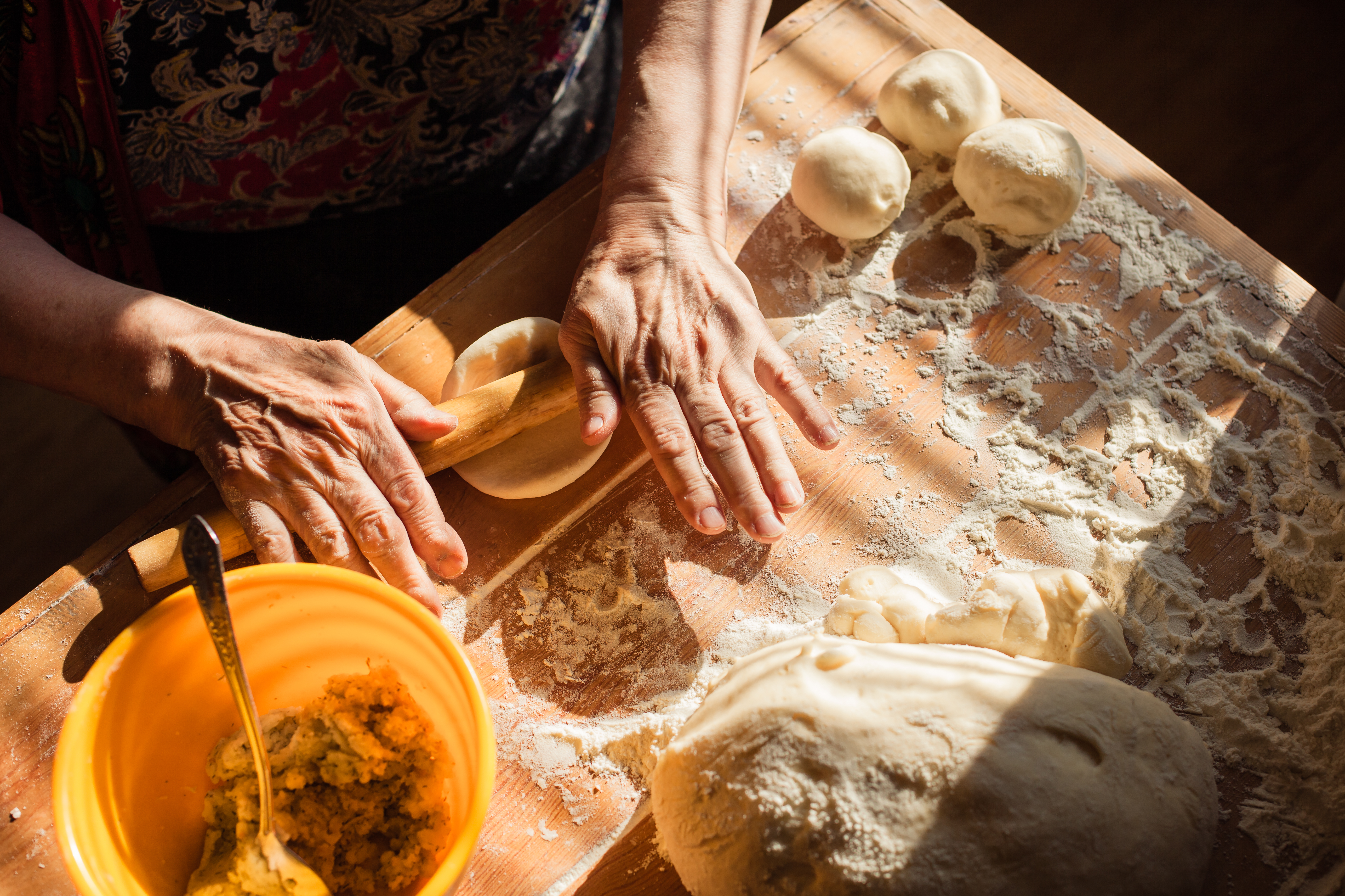 Hands rolling out dough on a sunlit kitchen counter.