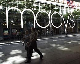 A Macy's window reflects pedestrians in Boston.