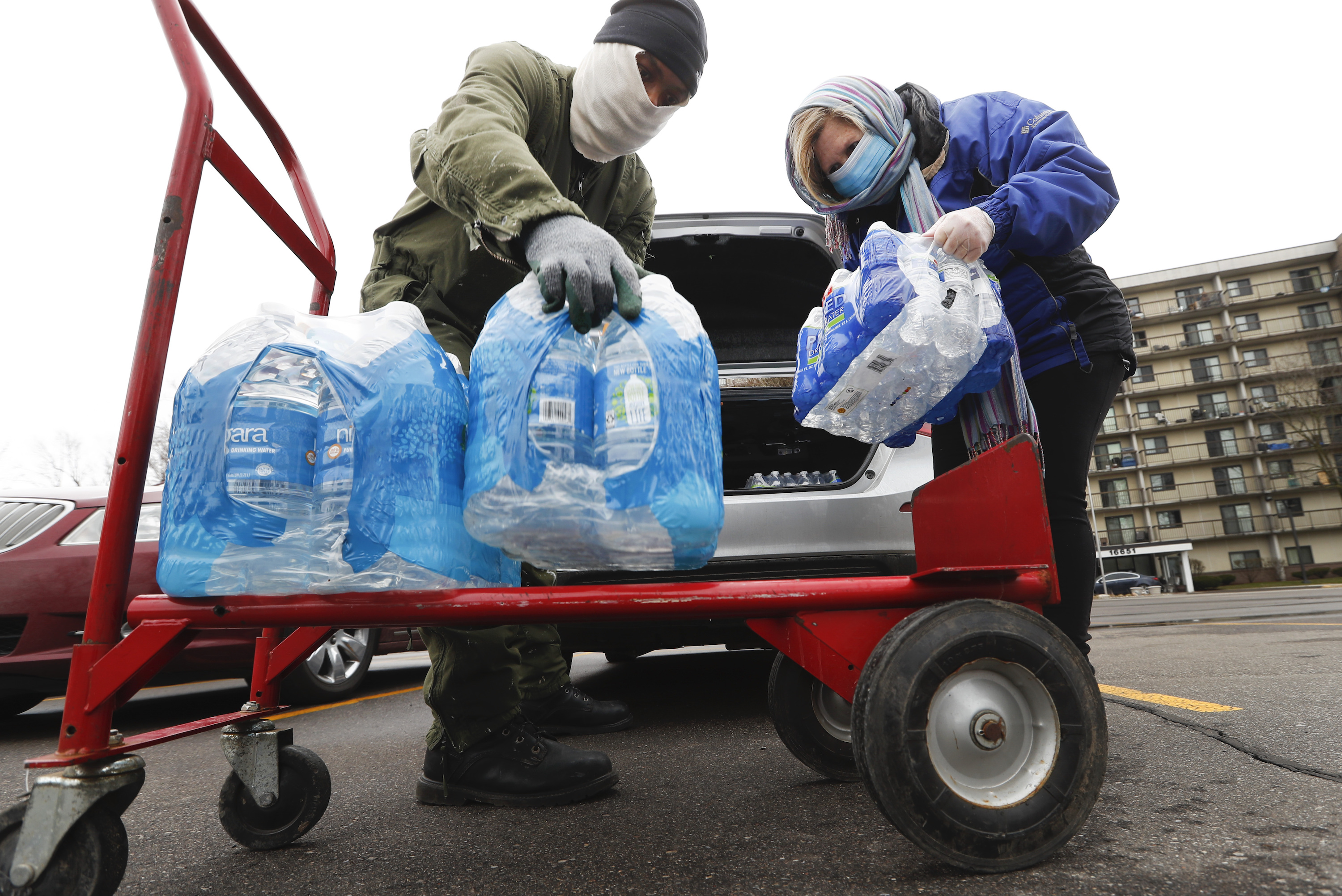 Two people wearing face masks place cases of bottled water from a van onto a dolly.