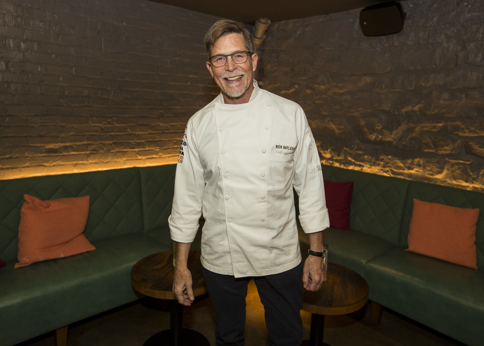 A man in a white chef's shirt standing.