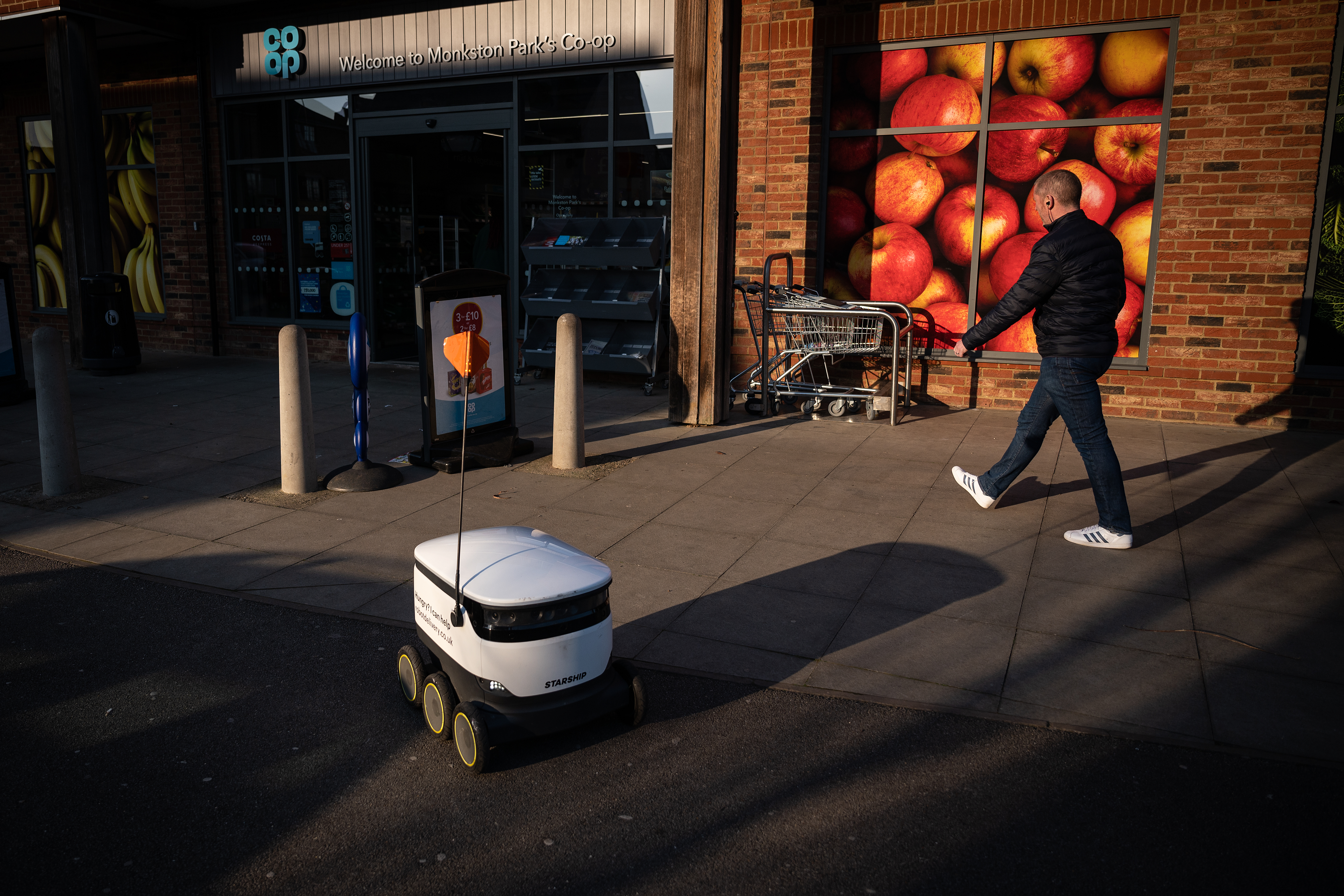 A delivery robot drives by a man walking.