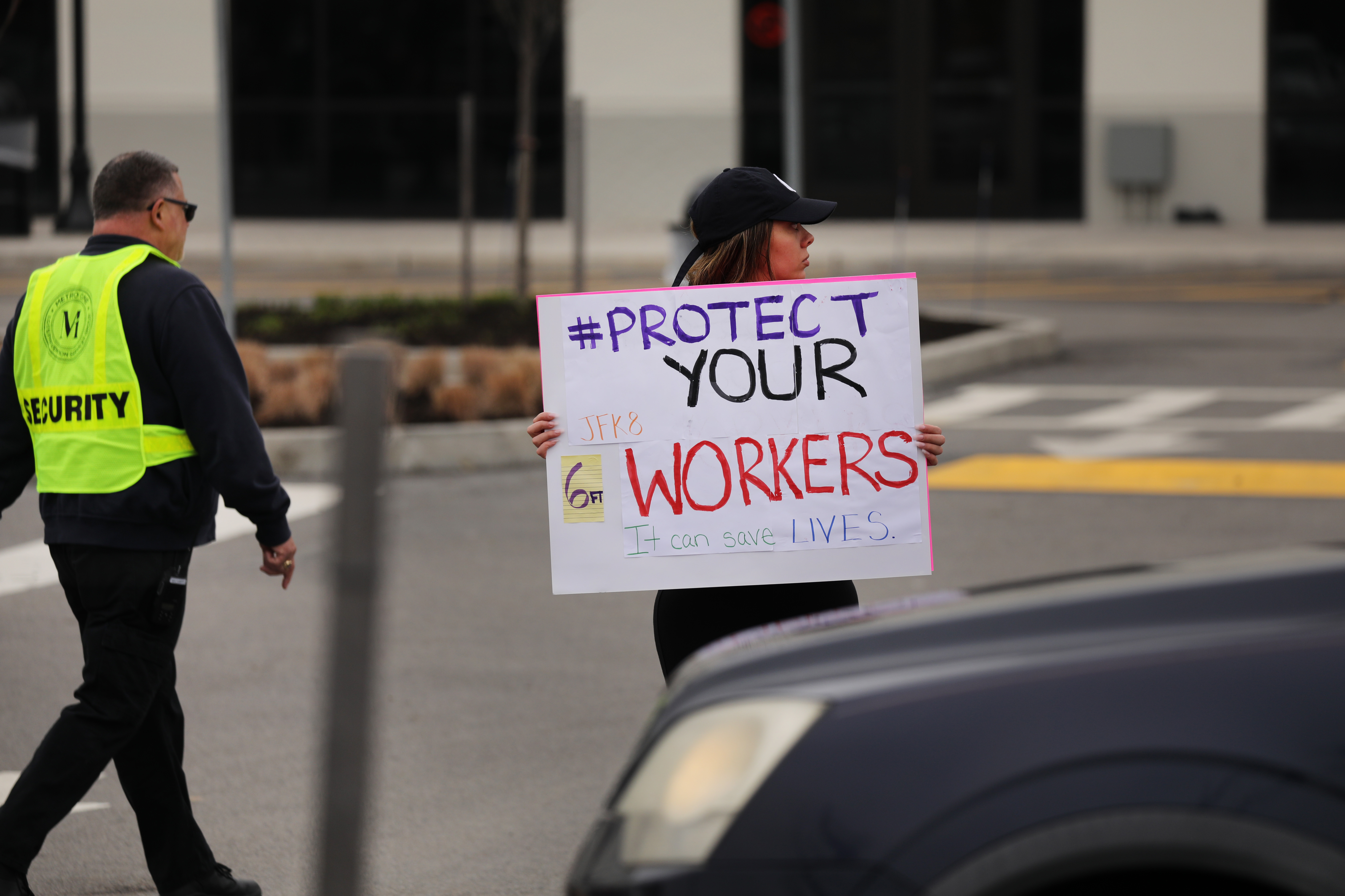 "A protester holds a sign that reads, ""Protect your workers."""