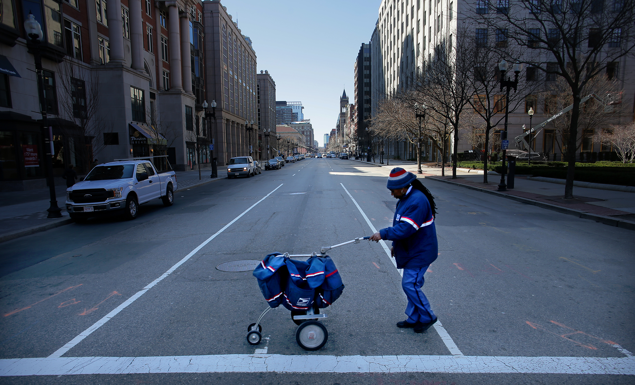 A USPS letter carrier crosses a quiet Boylston Street with greatly reduced foot and vehicle traffic in Boston on March 18, 2020.