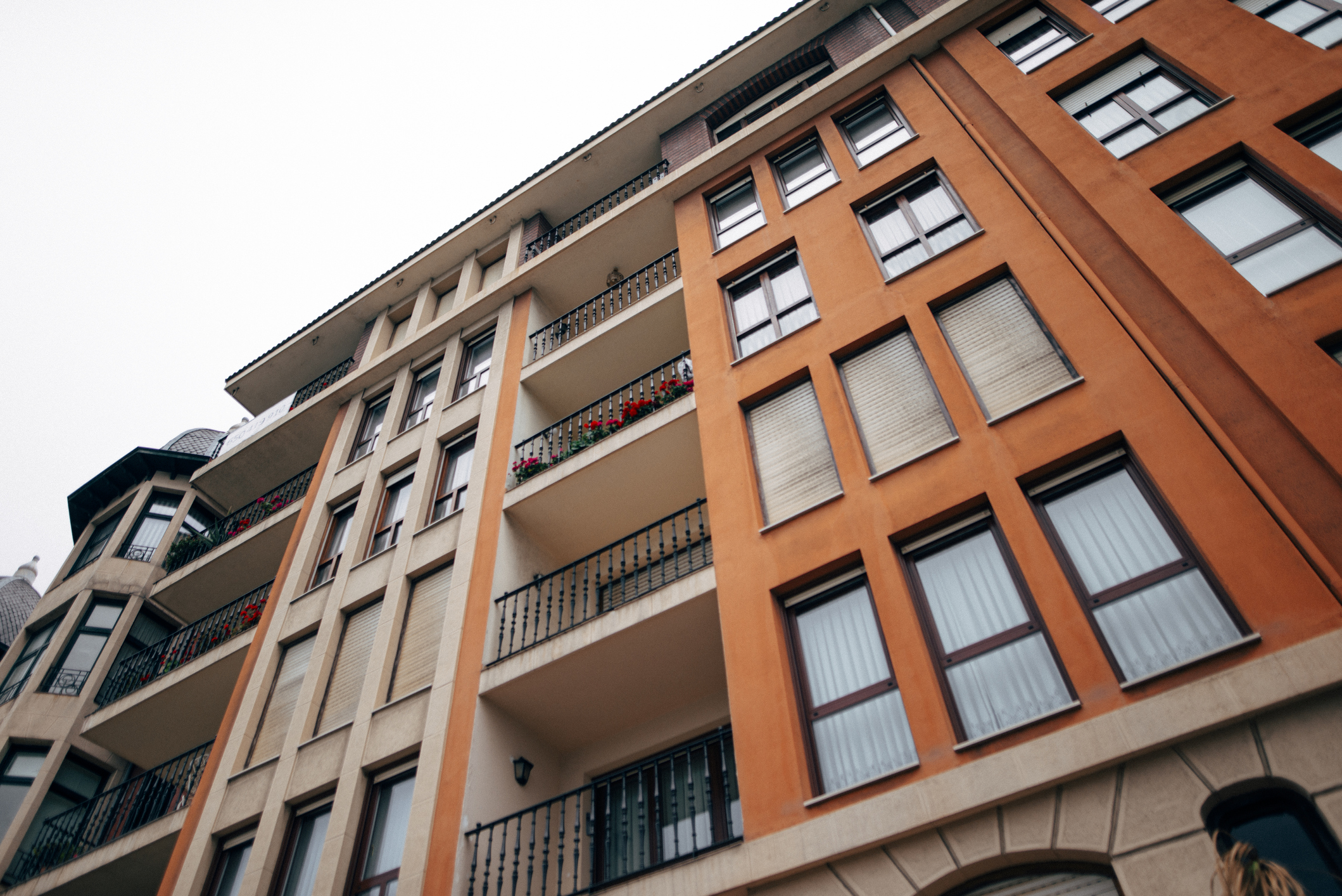 A five-story apartment building shot from the ground. It has two columns with windows separated by a balcony on each floor.