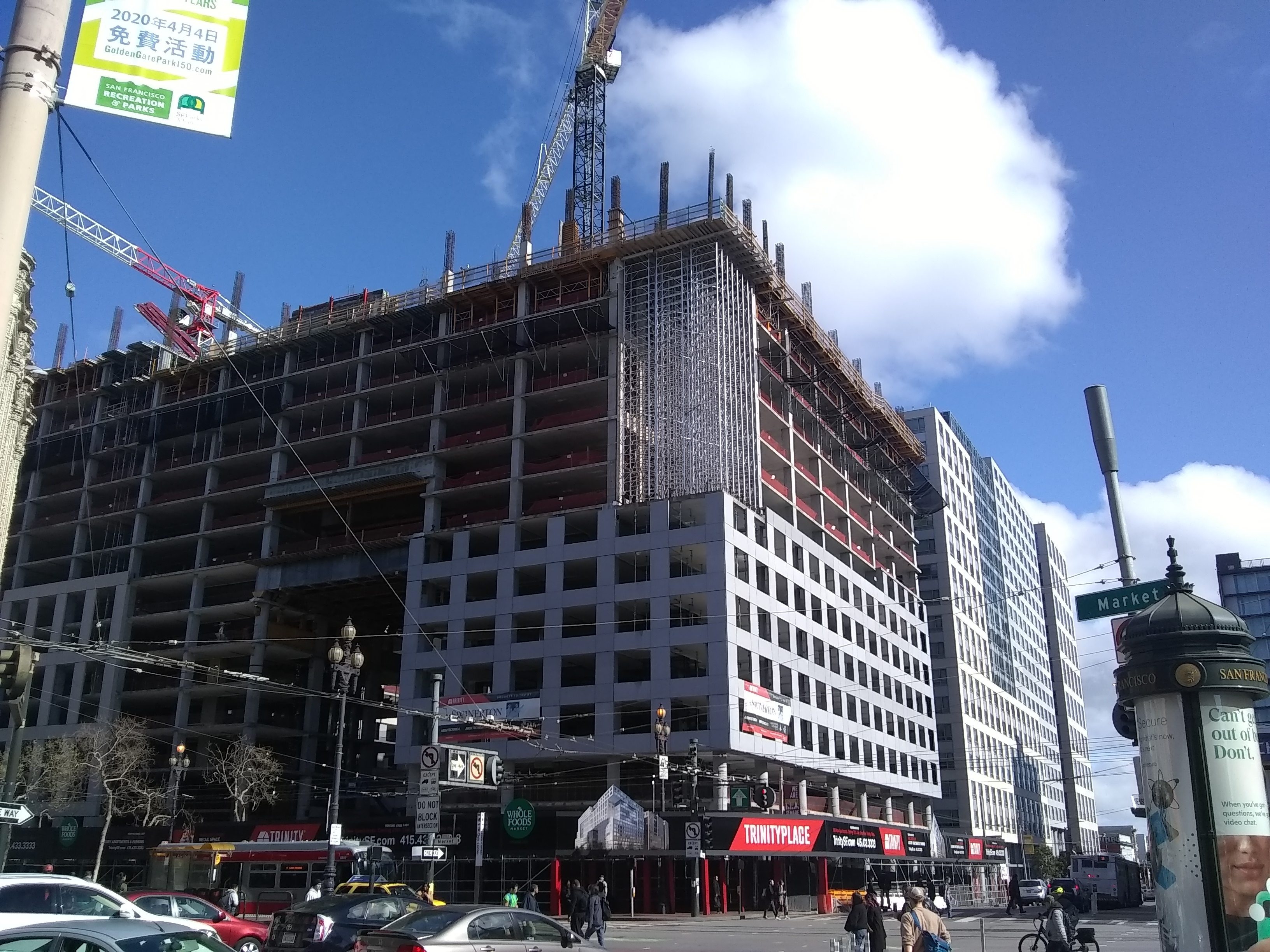 A mid-rise SF building, half-constructed, with a huge construction crane on top.