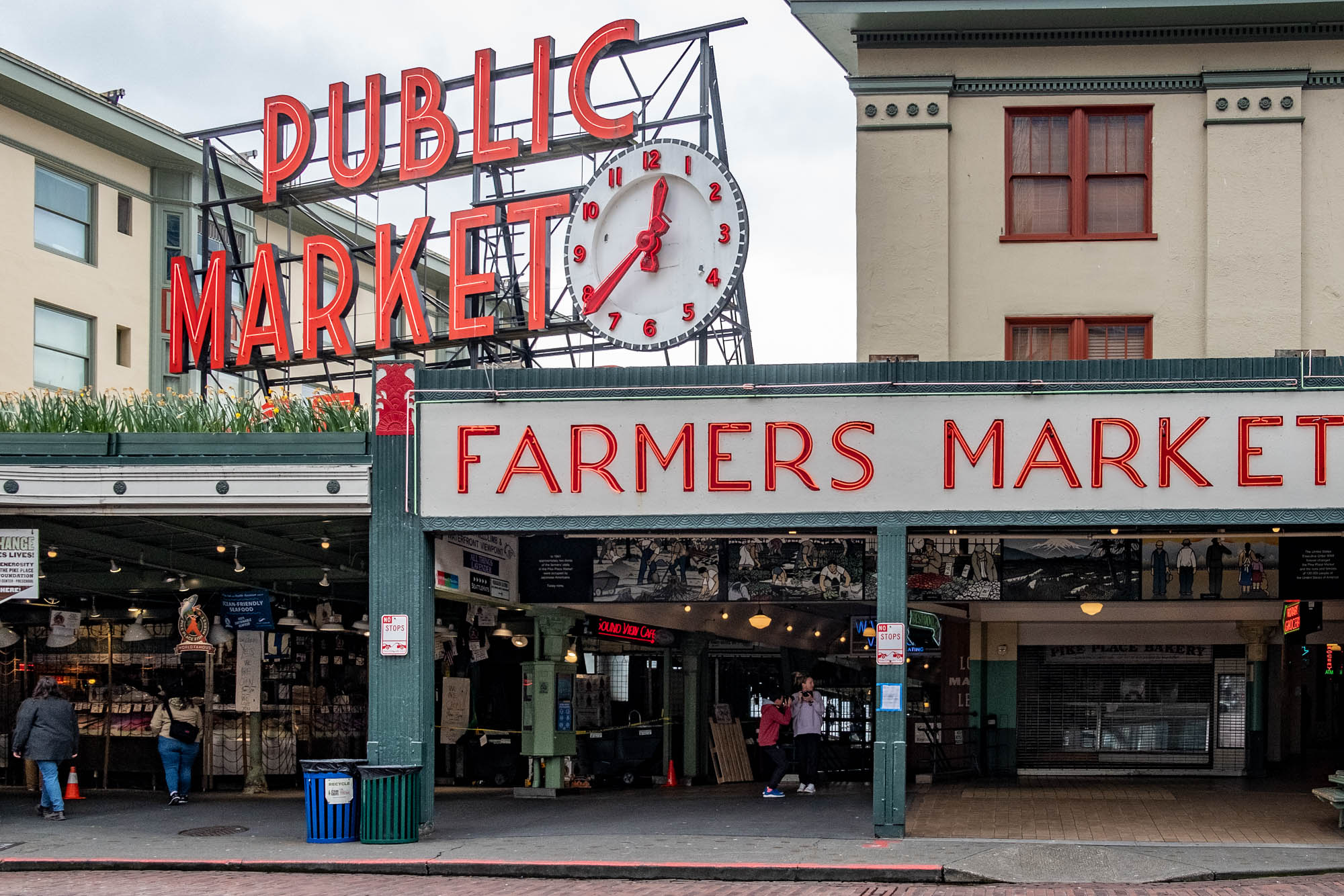 Pike Place Market on a cloudy day, with a view of the iconic sign and clock