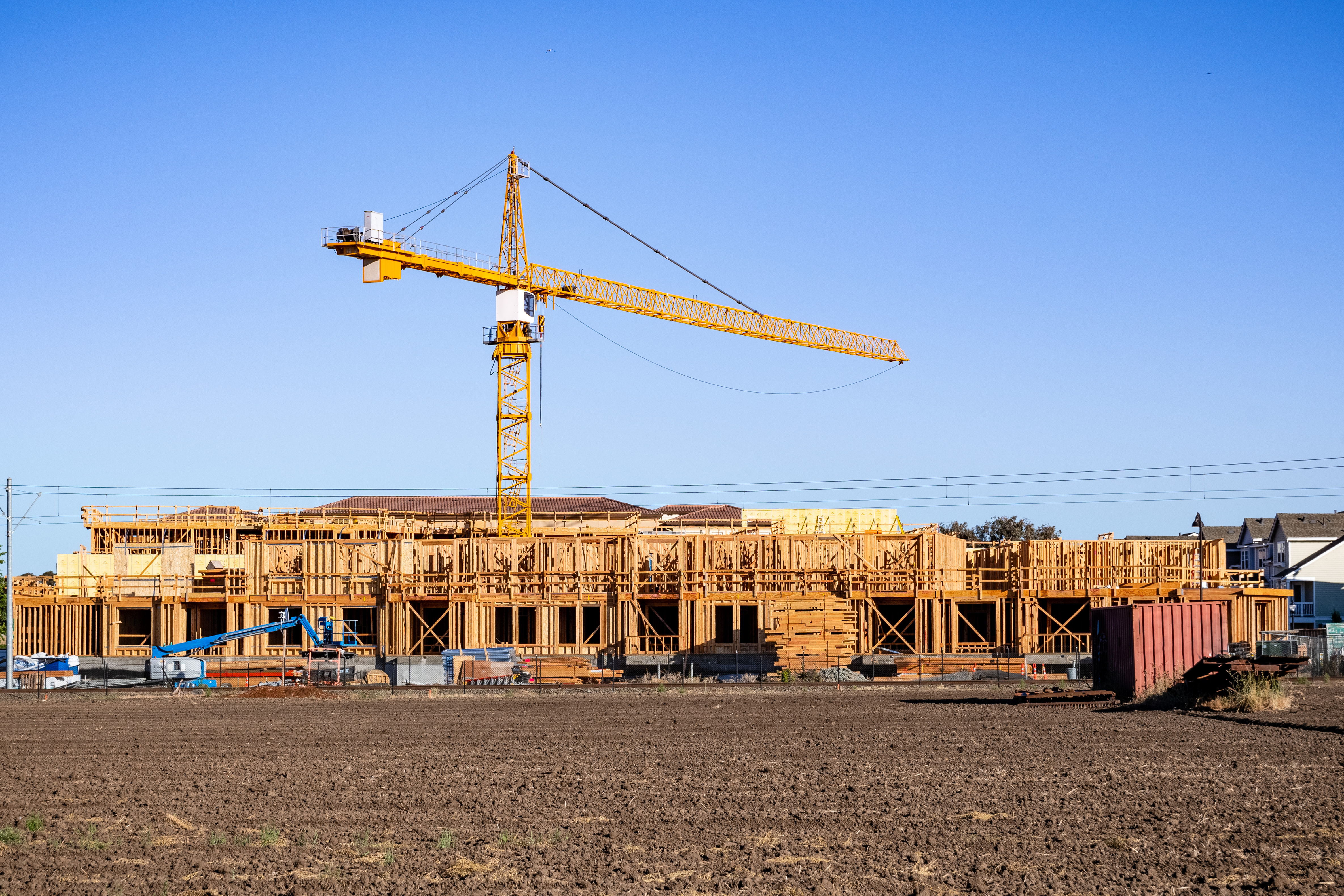 Construction of mid-rise buildings with a large yellow crane hovering above.