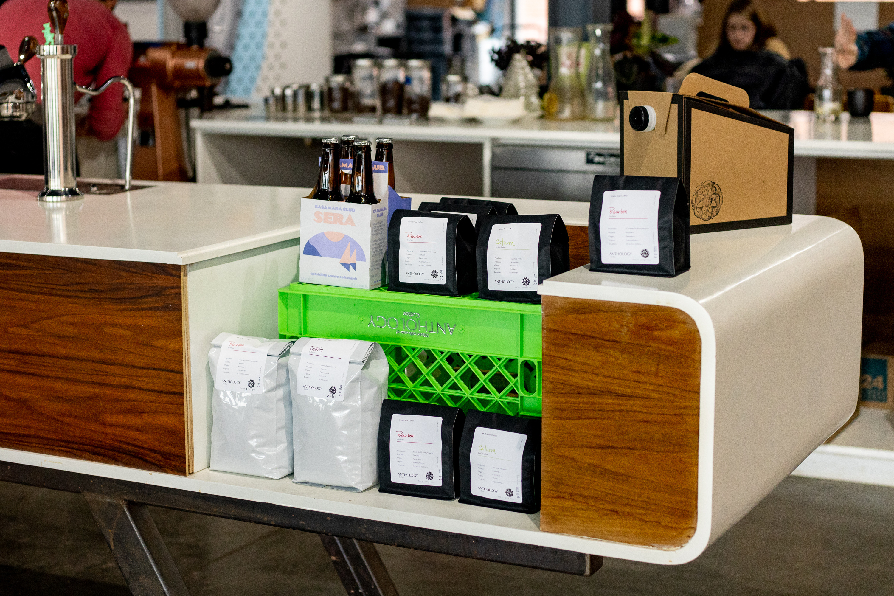 Bags of coffee at the white and wood paneled mid-century bar inside Anthology Coffee.