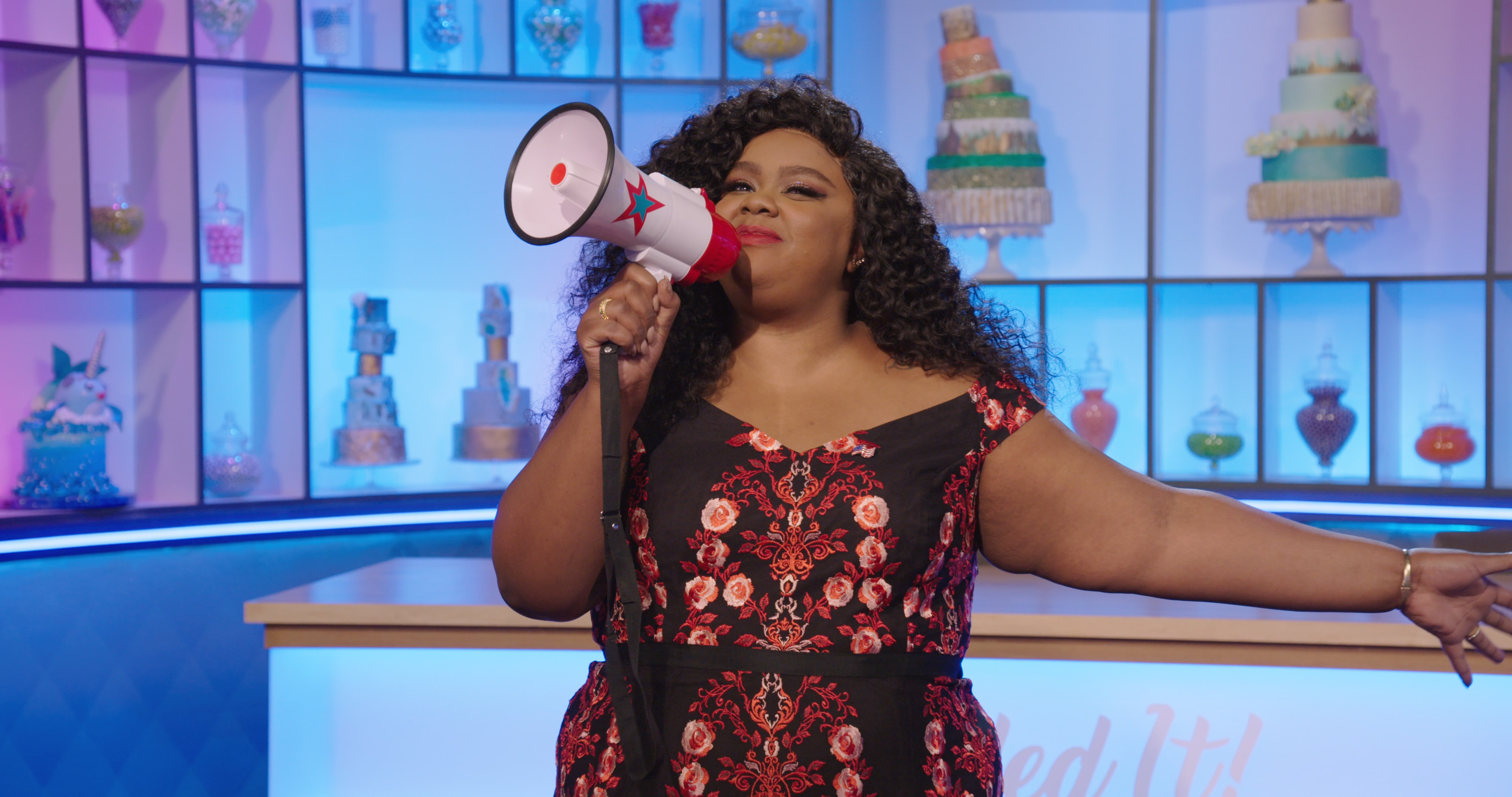 Nicole Byer holding a megaphone