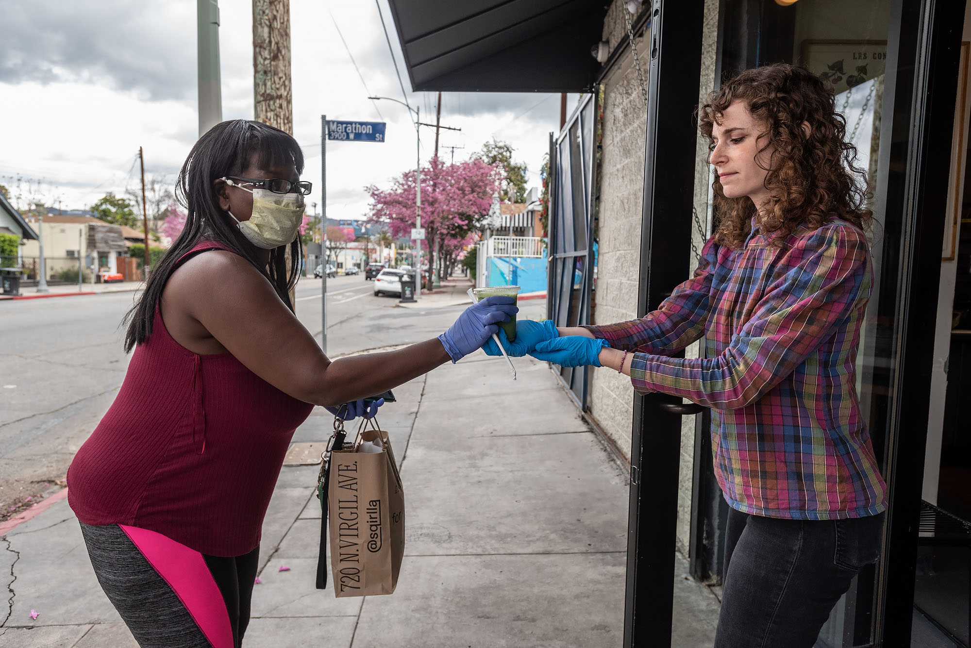 A worker hands food to a delivery driver in a mask and gloves.