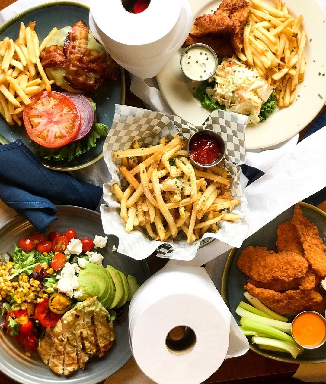 Overhead view of a table full of plates of pub fare and rolls of toilet paper