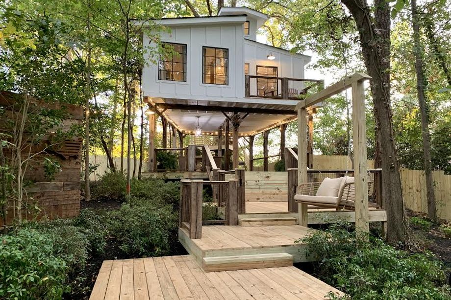 A white elevated treehouse in the trees.