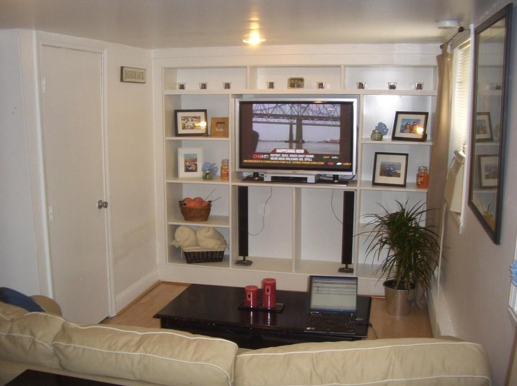 A living room with a couch facing built-in shelves with a TV.
