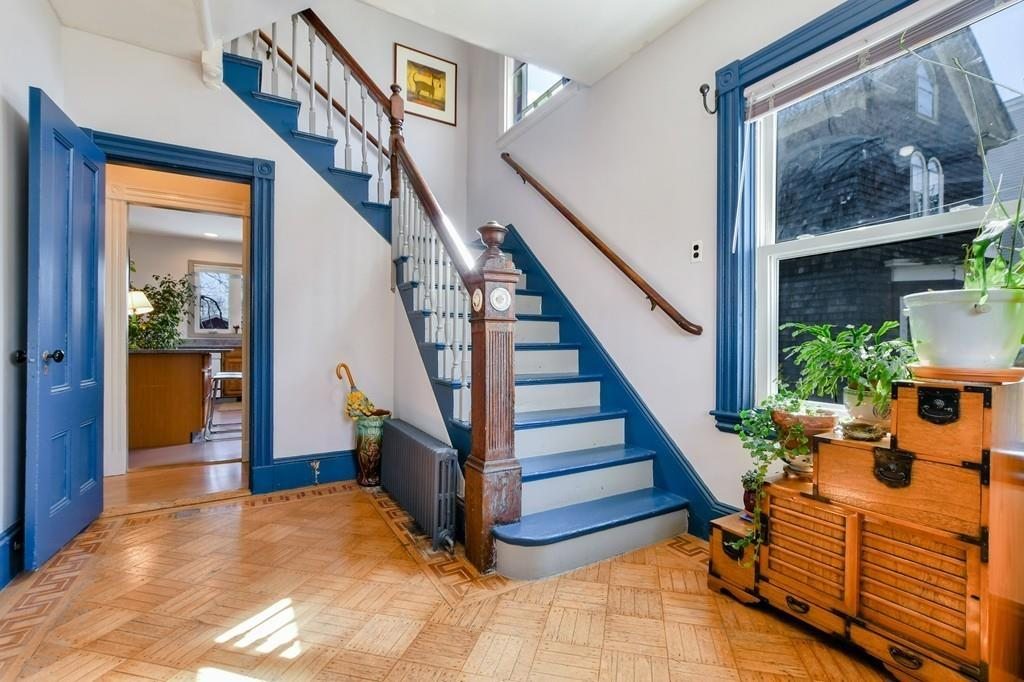 An entry foyer with a brightly colored stairwell and  an opened door.