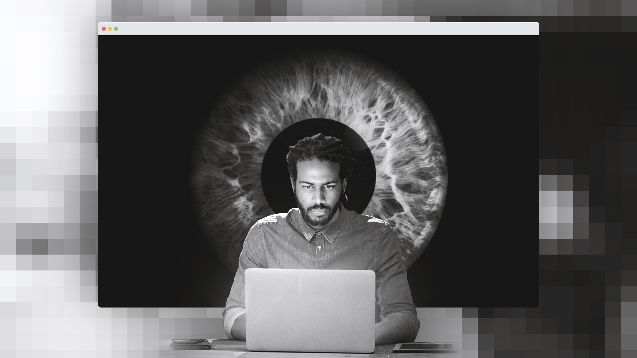 A man looks at a laptop while a giant eye behind him stares.