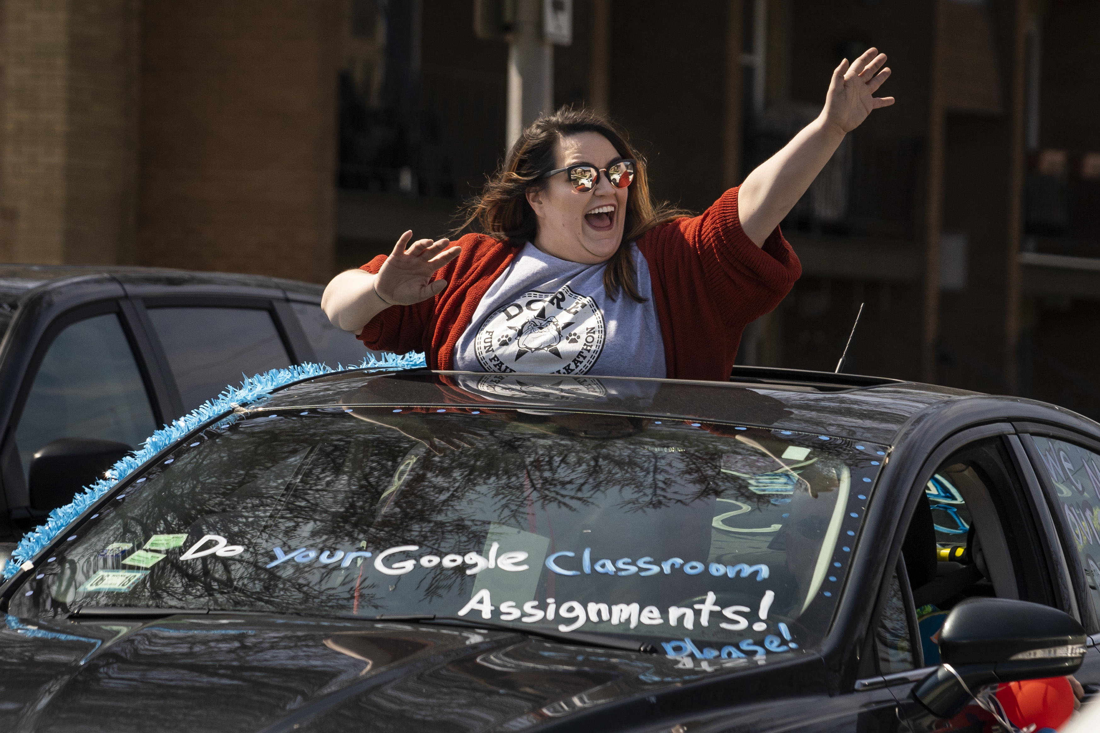 Teachers and staff at Dore Elementary School parade around the neighborhood Thursday afternoon, waving to families and children in the Southwest Side community.