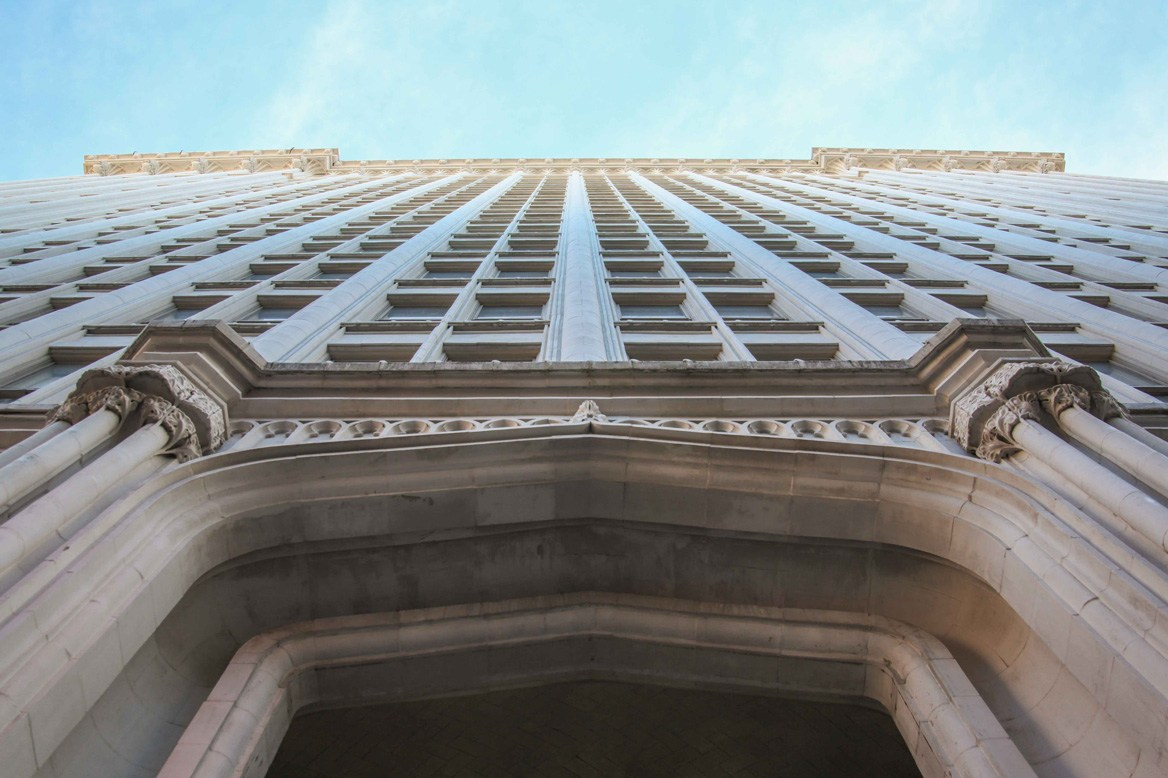 Looking up the Gothic Revival facade, composed of white terra cotta.