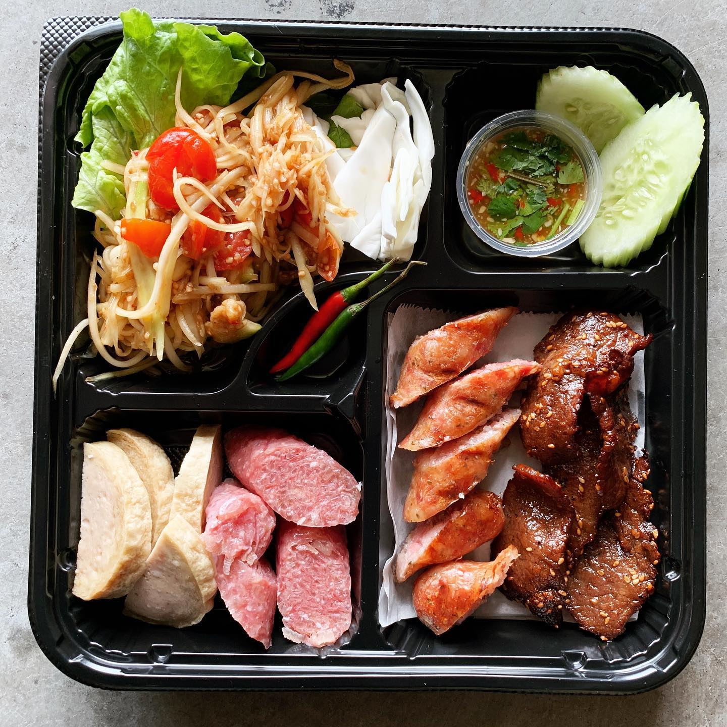 papaya salad, Lao sausage, beef jerky, crispy pork belly, and pickled cucumbers in a to-go container at Snackboxe Bistro in Doraville, GA