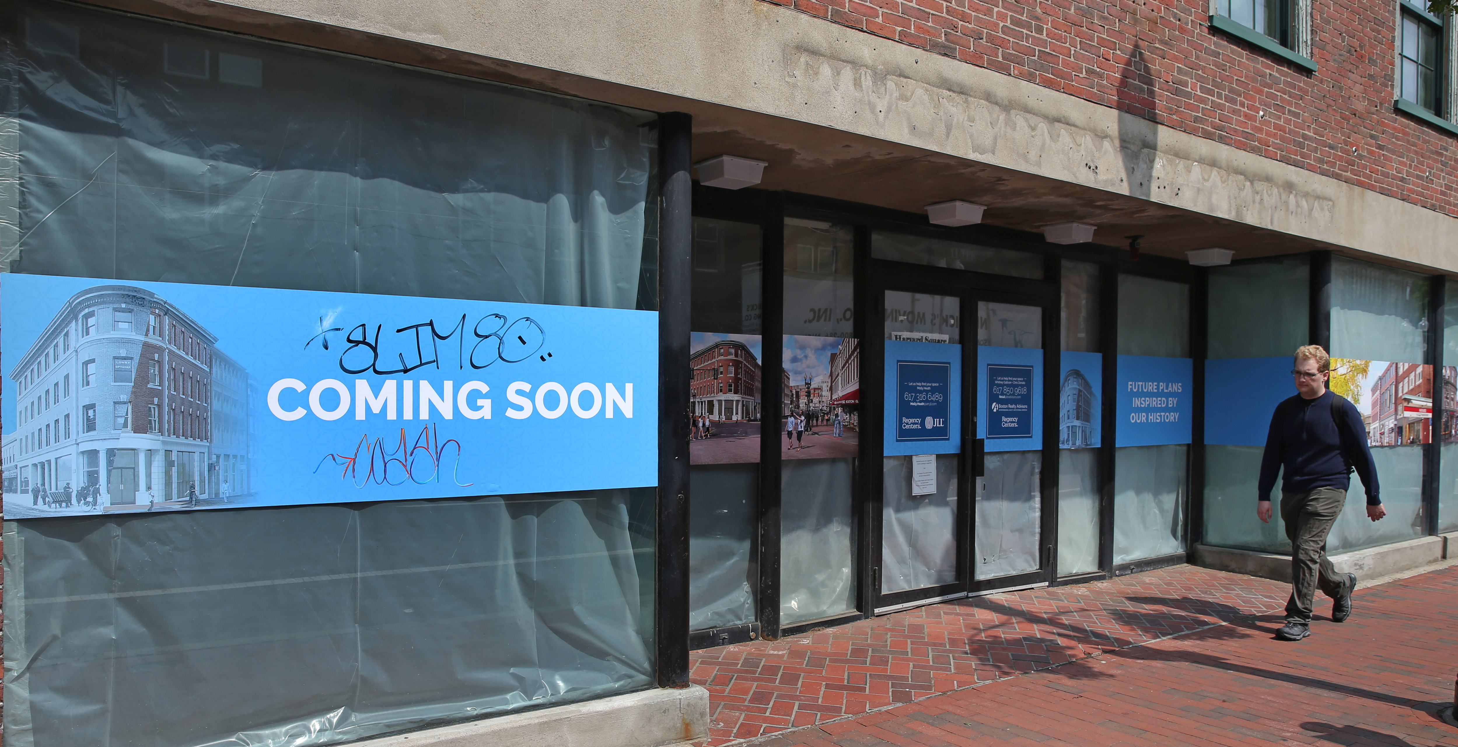 """The side of a building up close from the sidewalk, and there's construction casing across its windows and a sign that reads """"Coming soon."""""""