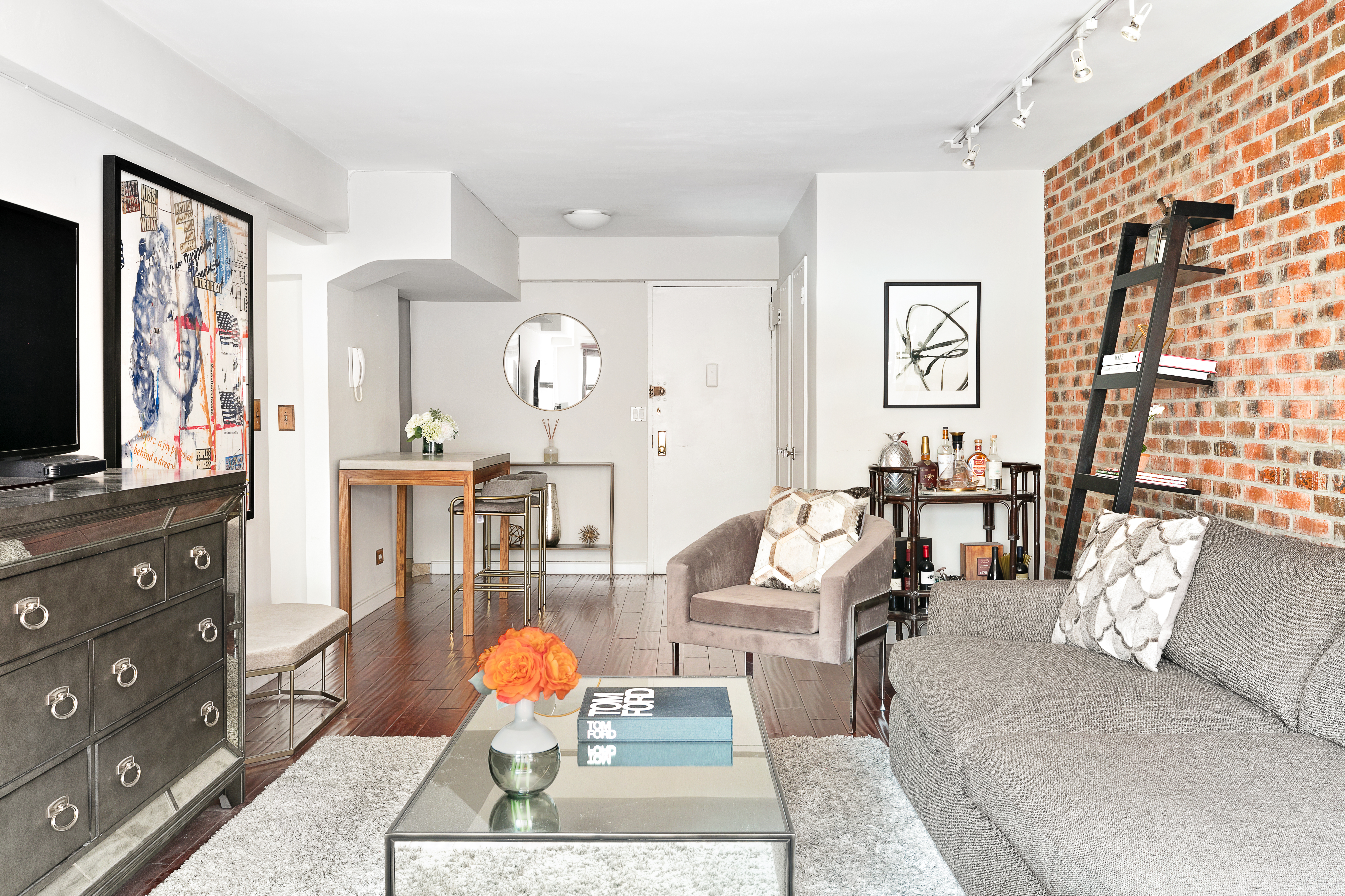 A living with a grey couch, a grey rug, a coffee table, and exposed brick.